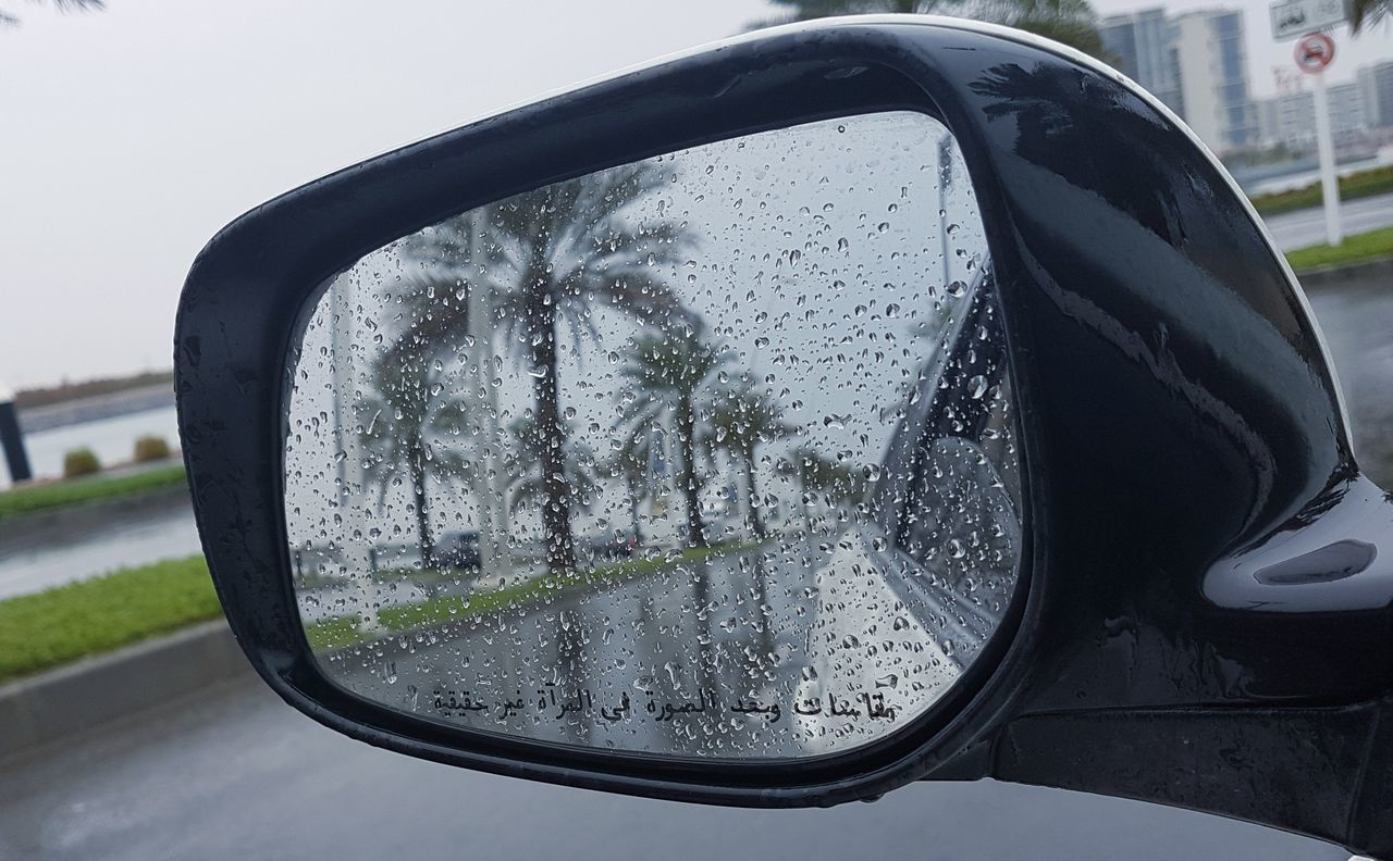 side-view mirror, glass - material, car, transparent, window, reflection, rain, land vehicle, transportation, wet, mode of transport, car interior, mirror, vehicle interior, weather, rainy season, vehicle mirror, day, water, road, travel, no people, raindrop, drop, close-up, nature, outdoors, sky