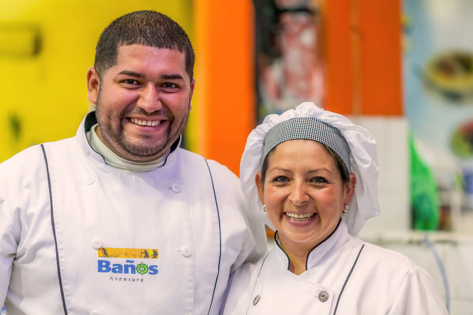 Banos De Agua Santa, Ecuador - 23 June 2016: Unidentified Happy Chef Couple Or Cooks Smiling To The Camera, Banos De Agus Santa Public Market, Ecuador, South America Adult Adults Only BañosEcuador Business Finance And Industry Cheerful Chef Community Outreach Cooks Couple Food Friendship Happiness Happiness Lifestyles Looking At Camera Love Men Outdoors People Portrait Smile Smiling Togetherness Two People Women