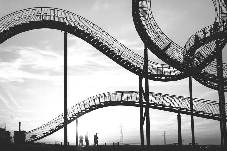 Rollercoaster Amusement Park Architecture City Outdoors Day People Tiger And Turtle Tiger & Turtle Fine Art Fineart First Eyeem Photo Black And White Monochrome Monochromatic Industrial Art Arts Culture And Entertainment Construction Loop Leisure Activity People Together Landmark Art Is Everywhere