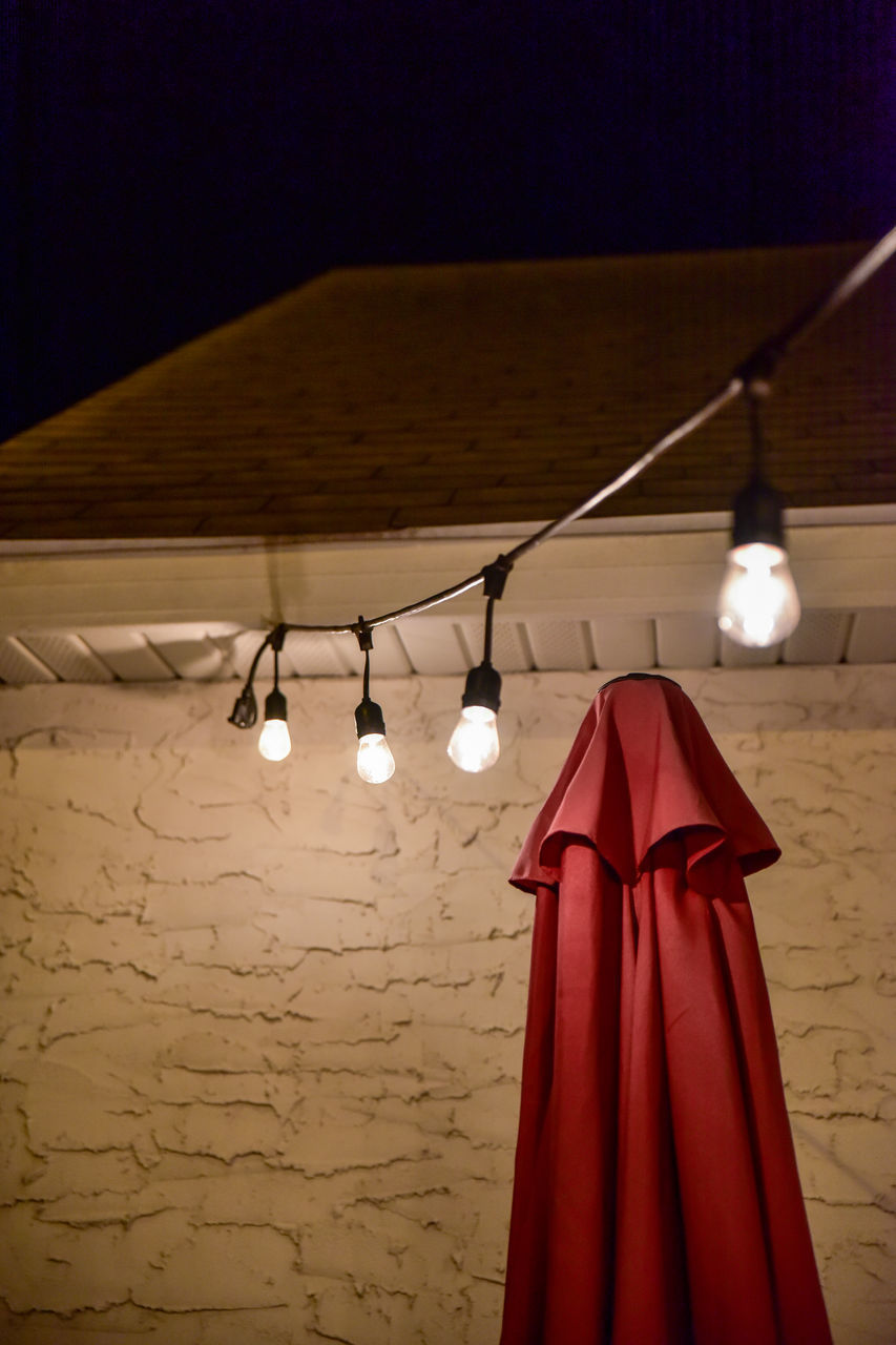 Red Parasol Below Illuminated Light Bulbs Hanging From Cable At Night In Back Yard