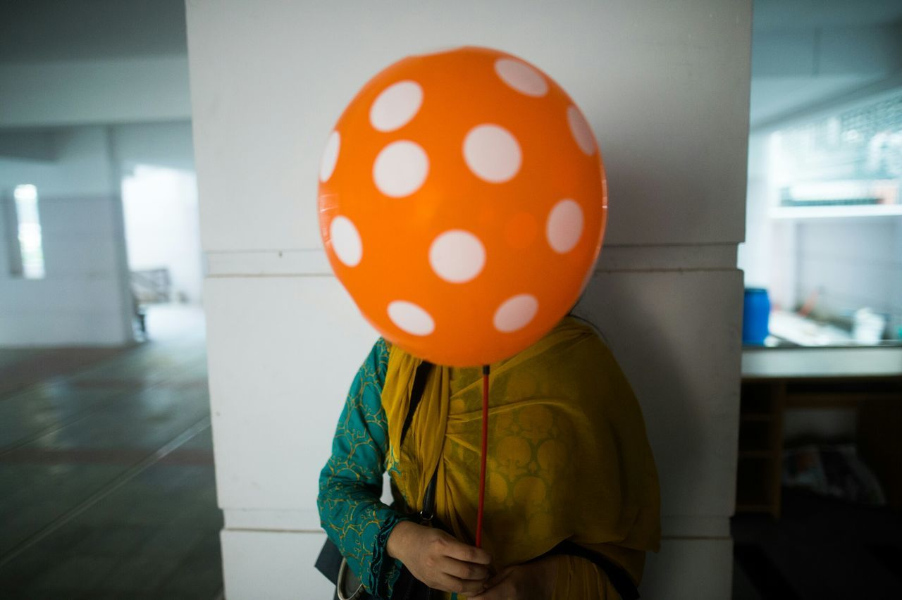 Close-Up Of Woman Holding Balloon In Front Of Her Face