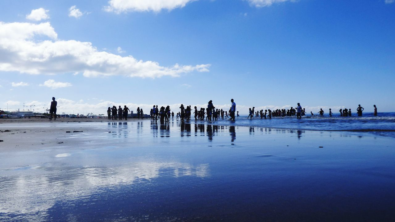 Reflection Sky Beach Outdoors Cloud - Sky Day Water Nature Large Group Of Animals Sea Low Tide Adult People Beach Life Large Group Of People Vacation Time Silhouette Togetherness Adult Young Adult Children Playing On Beach Sand Walking Blue Sky