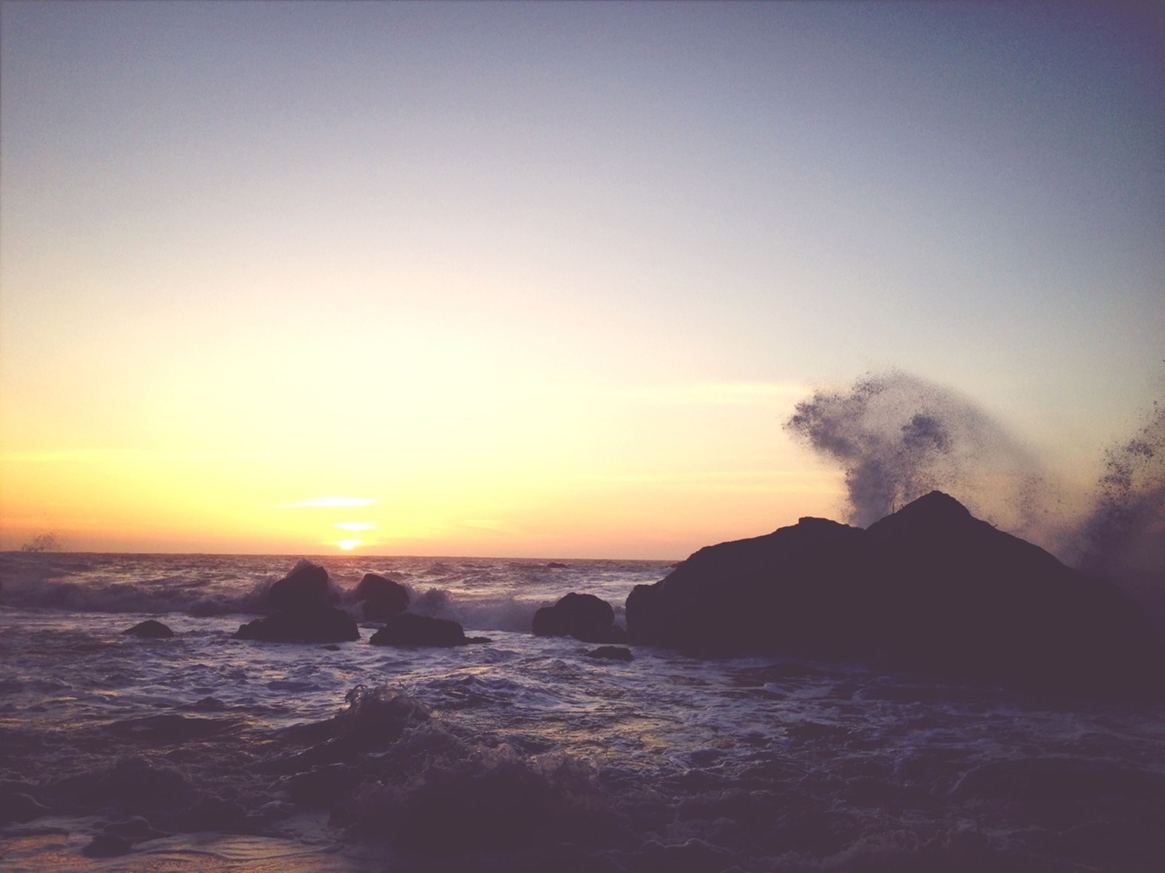 sea, water, scenics, sunset, horizon over water, beauty in nature, tranquil scene, rock - object, tranquility, rock formation, nature, idyllic, sky, waterfront, clear sky, orange color, wave, copy space, silhouette, rock