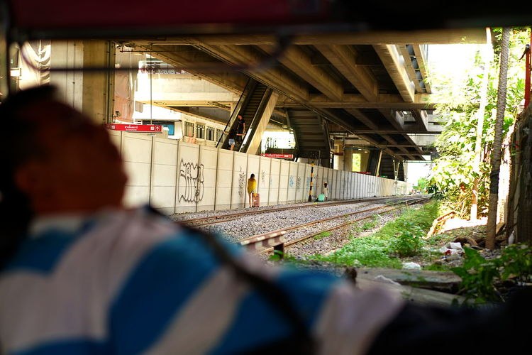 Bangkok Built Structure Mode Of Transport Outdoors Railroad Track Real People Sleeping Street Photography Transportation Tuktukdriver Woman With Suitcase