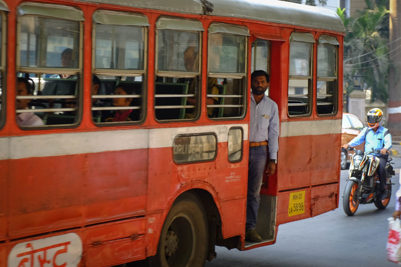 real people, transportation, mode of transport, land vehicle, men, day, red, outdoors, stationary, standing, mammal
