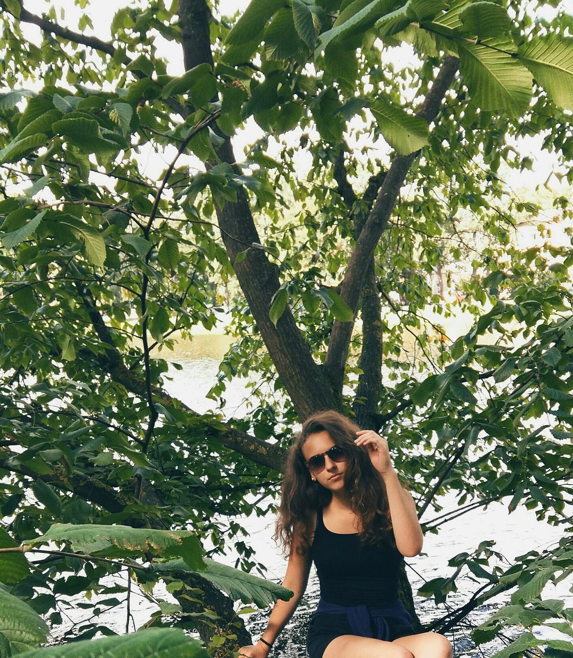 tree, young women, young adult, front view, real people, one person, lifestyles, smiling, casual clothing, looking at camera, leisure activity, standing, portrait, beautiful woman, day, long hair, outdoors, growth, nature, plant, leaf, happiness, branch, beauty in nature, people