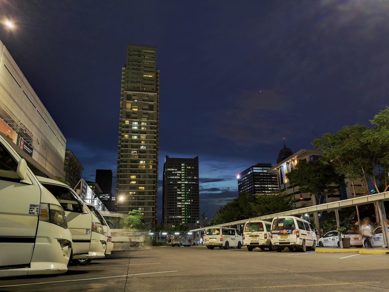 architecture, building exterior, transportation, car, mode of transport, city, built structure, land vehicle, modern, skyscraper, illuminated, road, street, night, outdoors, cityscape, travel destinations, no people, sky