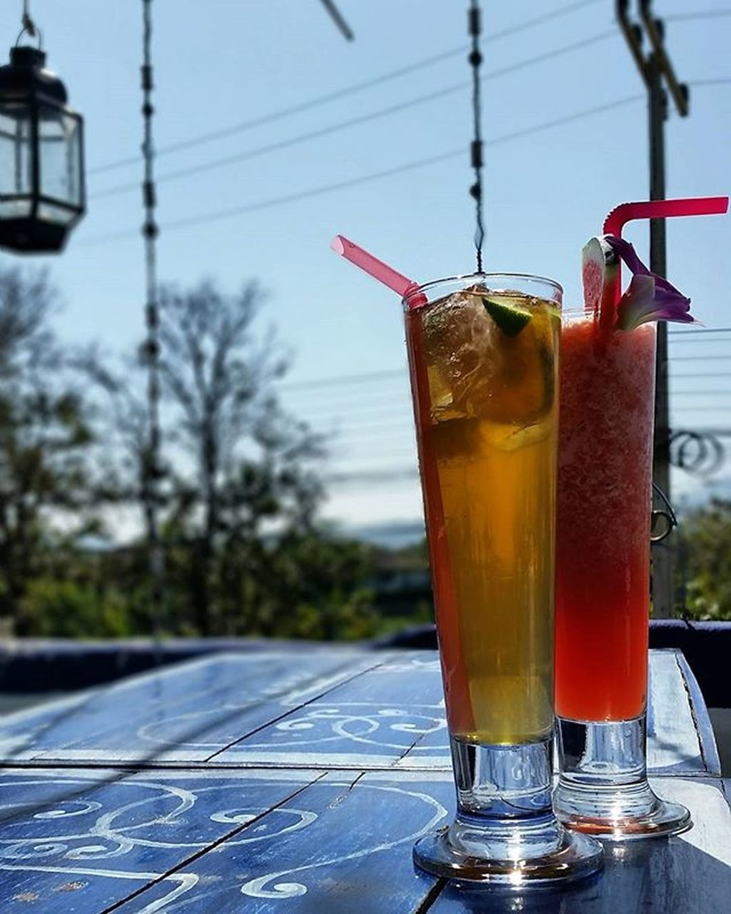 drink, drinking straw, refreshment, drinking glass, focus on foreground, food and drink, cocktail, cold temperature, table, close-up, outdoors, no people, day, alcohol, sky, tree, freshness
