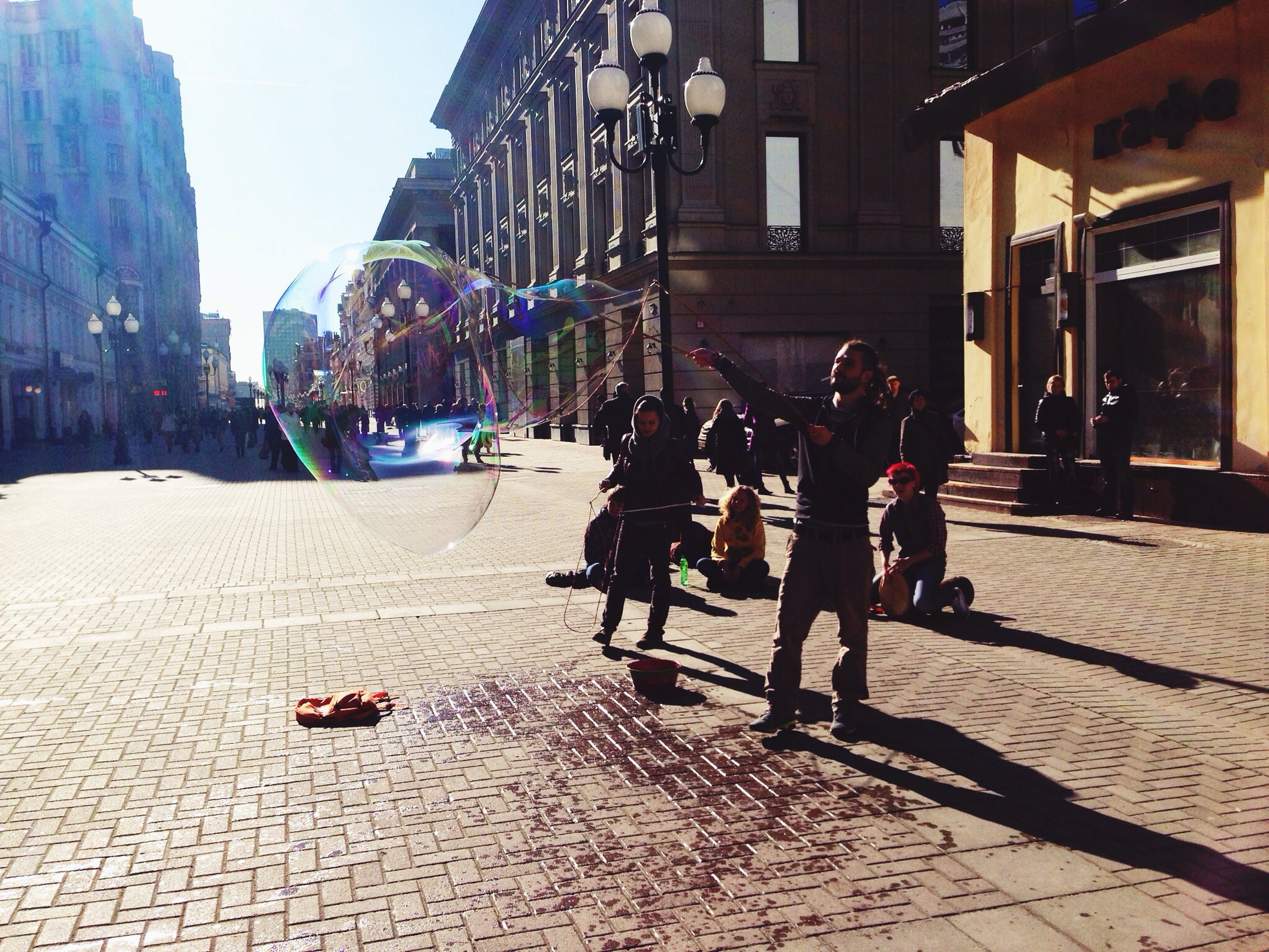 building exterior, architecture, built structure, lifestyles, street, men, leisure activity, city, shadow, full length, person, sunlight, walking, city life, sidewalk, cobblestone, outdoors, togetherness