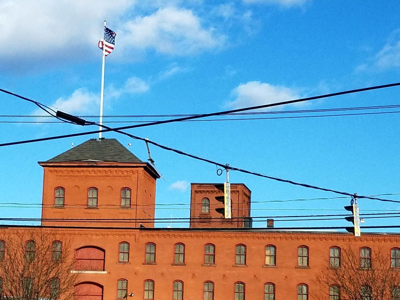 cable, built structure, building exterior, architecture, sky, flag, day, outdoors, no people, power line, cloud - sky, low angle view, patriotism, nature