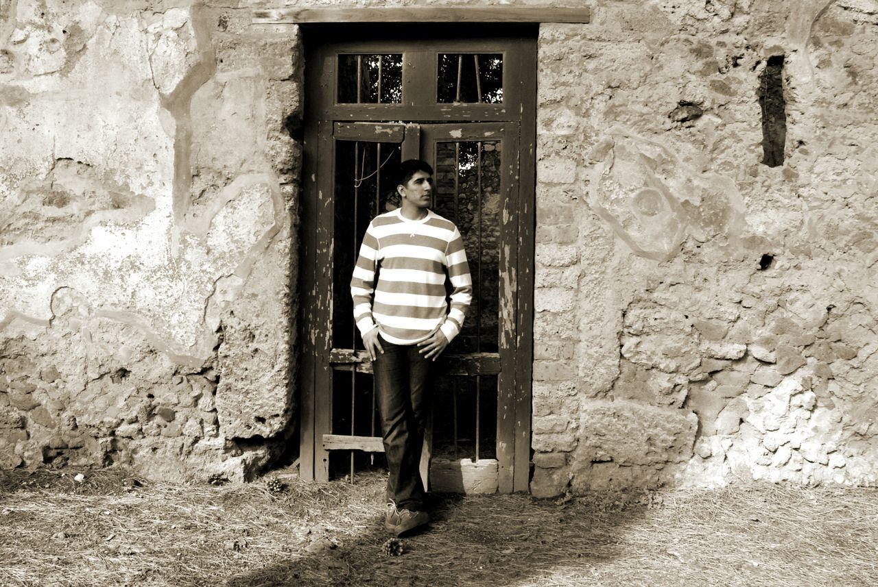Man With Hands In Pockets Standing Against Door Of Old House