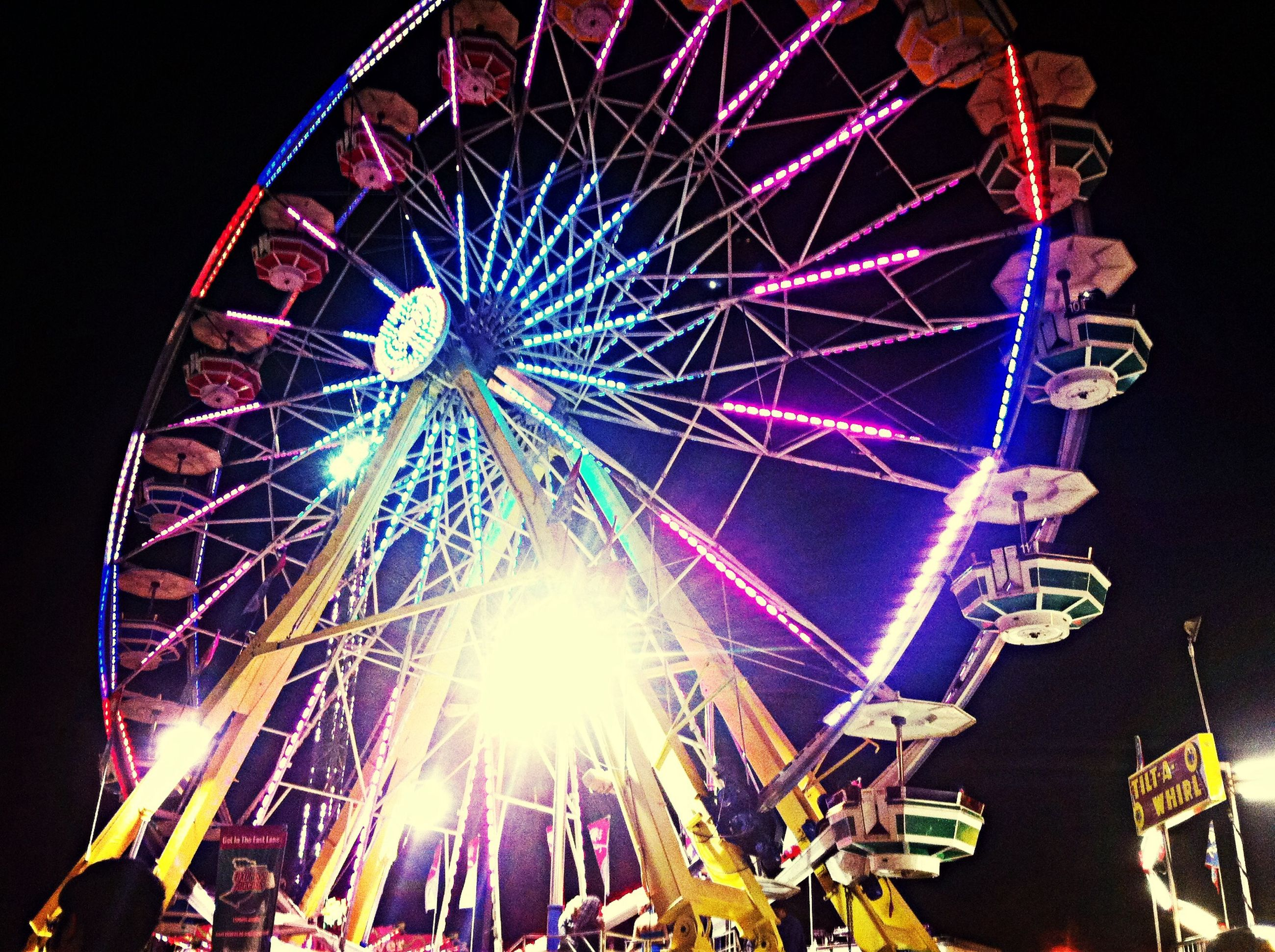 arts culture and entertainment, amusement park, amusement park ride, ferris wheel, night, illuminated, low angle view, sky, built structure, enjoyment, traveling carnival, architecture, fun, firework display, motion, clear sky, celebration, leisure activity, big wheel, outdoors