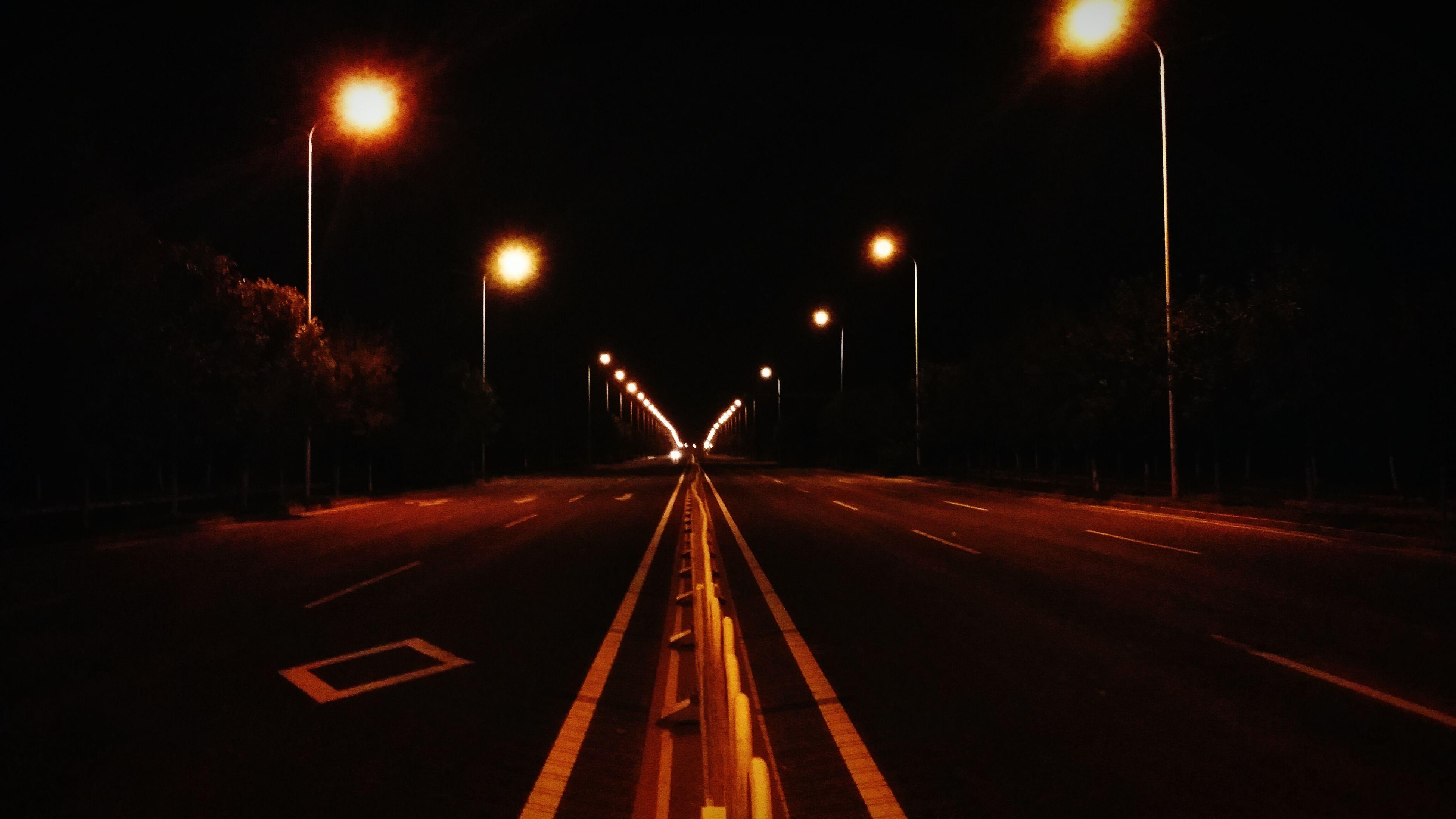 illuminated, transportation, the way forward, night, road, street light, diminishing perspective, road marking, vanishing point, lighting equipment, speed, long exposure, light trail, motion, street, red, sky, outdoors, road sign, tree
