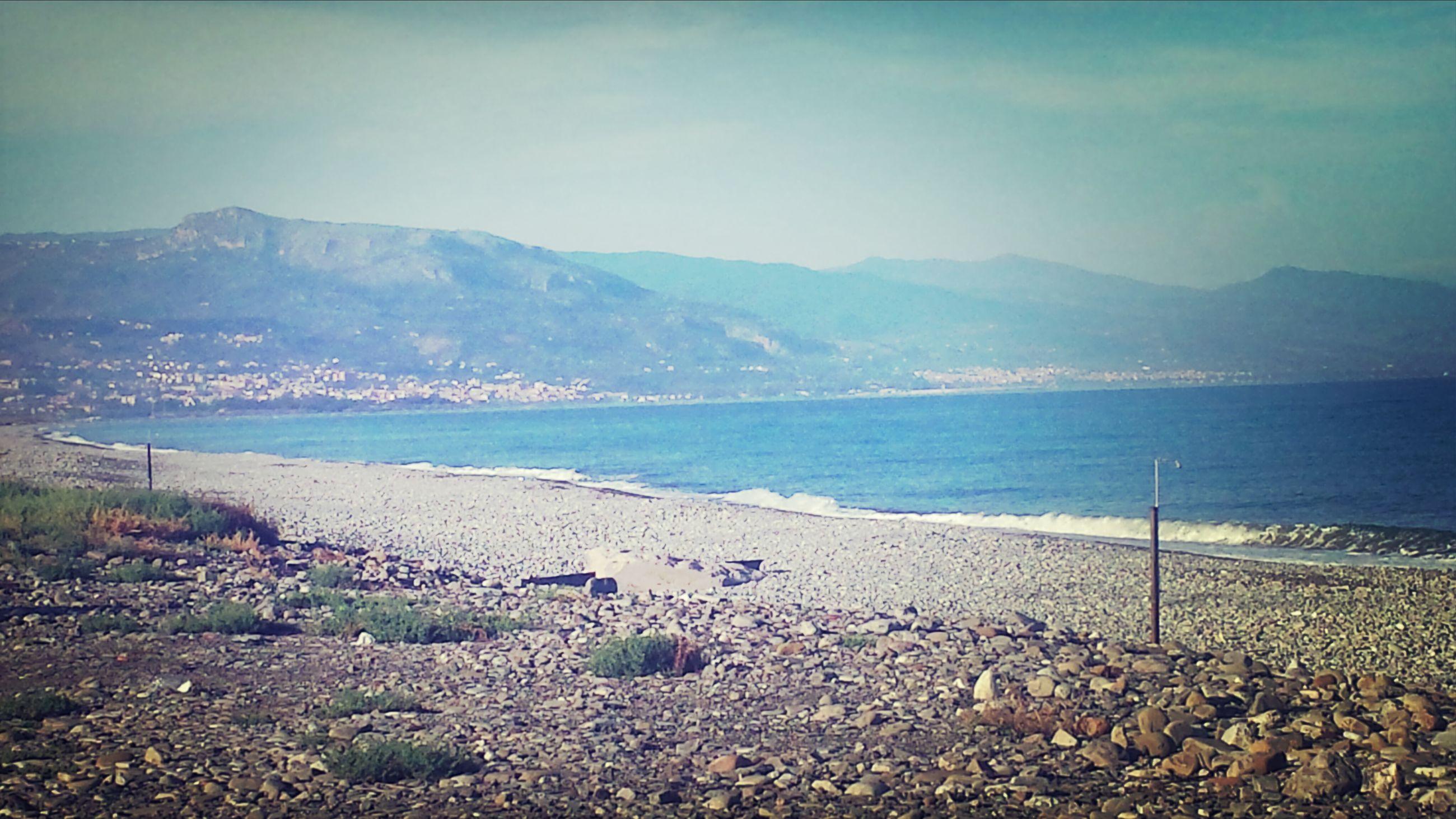 water, beach, sea, tranquil scene, mountain, scenics, shore, tranquility, sky, beauty in nature, sand, nature, coastline, mountain range, idyllic, rock - object, remote, non-urban scene, outdoors, day