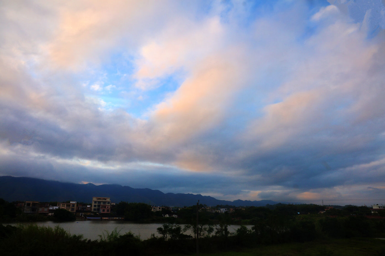 View Of Lake And Buildings Against Cloudy Sky