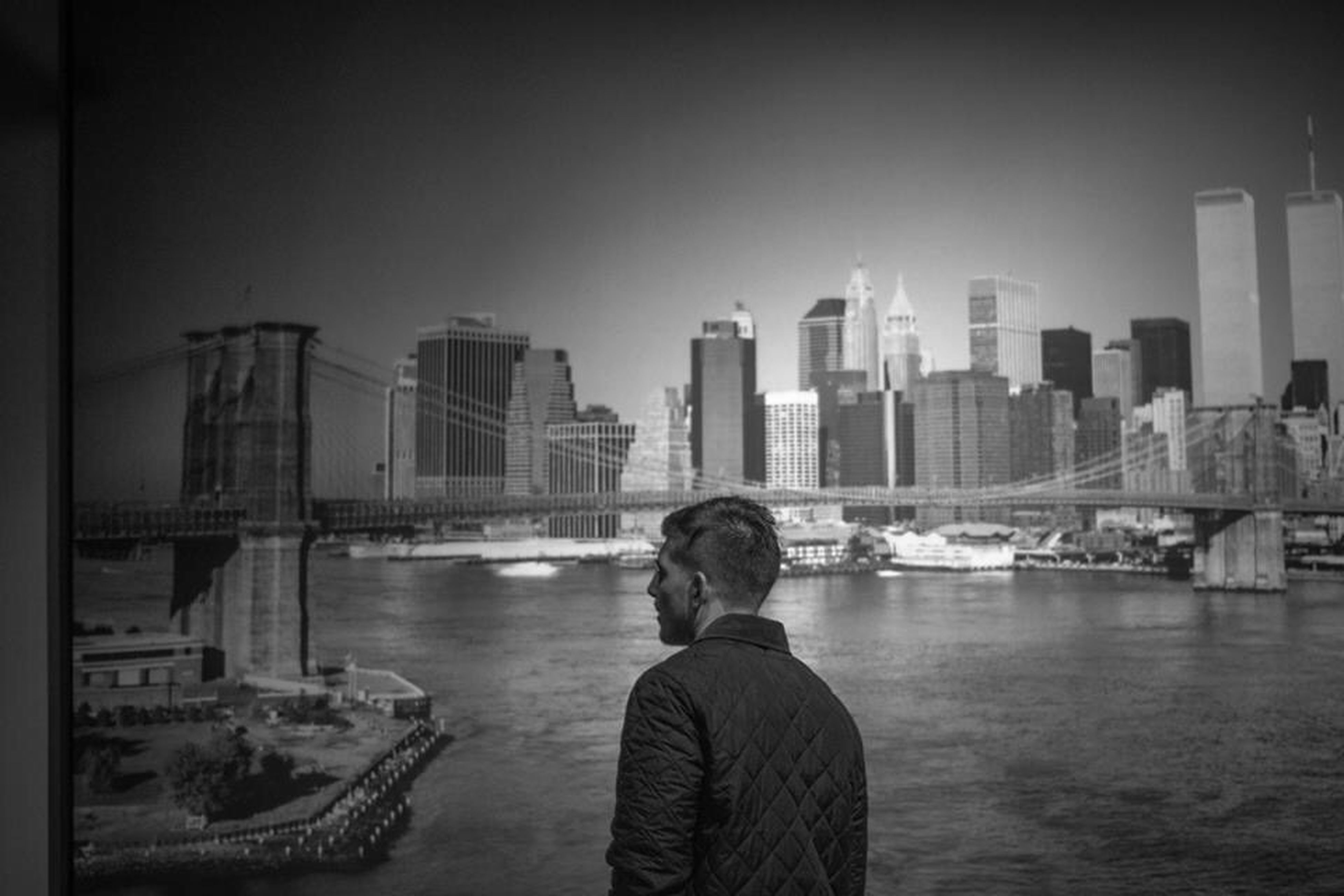 At first glance it is a man in front of the Skyline of Newyorkcity Pre-9/11 , then you follow his gaze to the end of the frame of what turns out to be just a photo. Then you realize the twin towers are actually gone in this photo, and your stomach sinks again. Cityscape Beauty