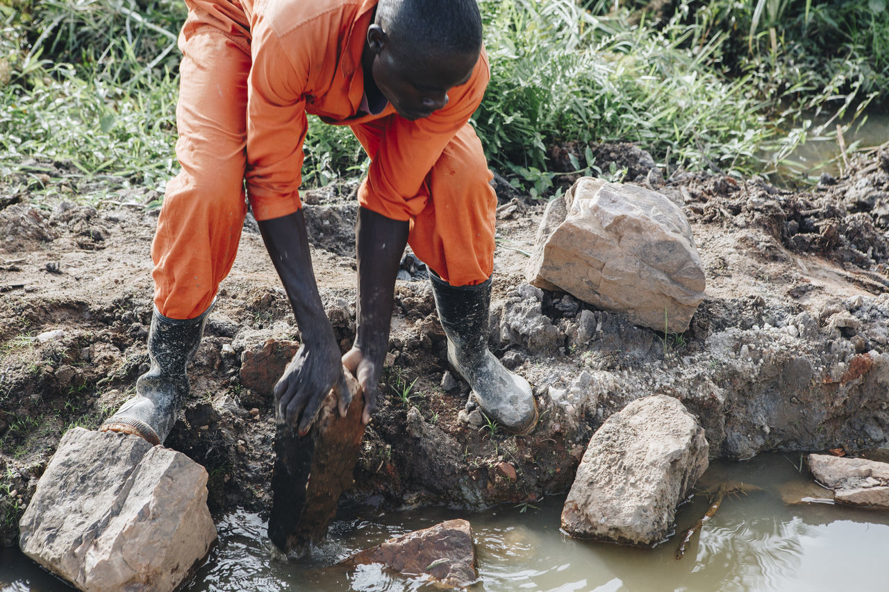 Africa African Building Building Site Construction Construction Industry Construction Site Construction Work Dirt Dirty Man Manual Worker Men Orange Color Protective Workwear Rocks Rubber Boots Stones Water Work Workers Working Working Hard