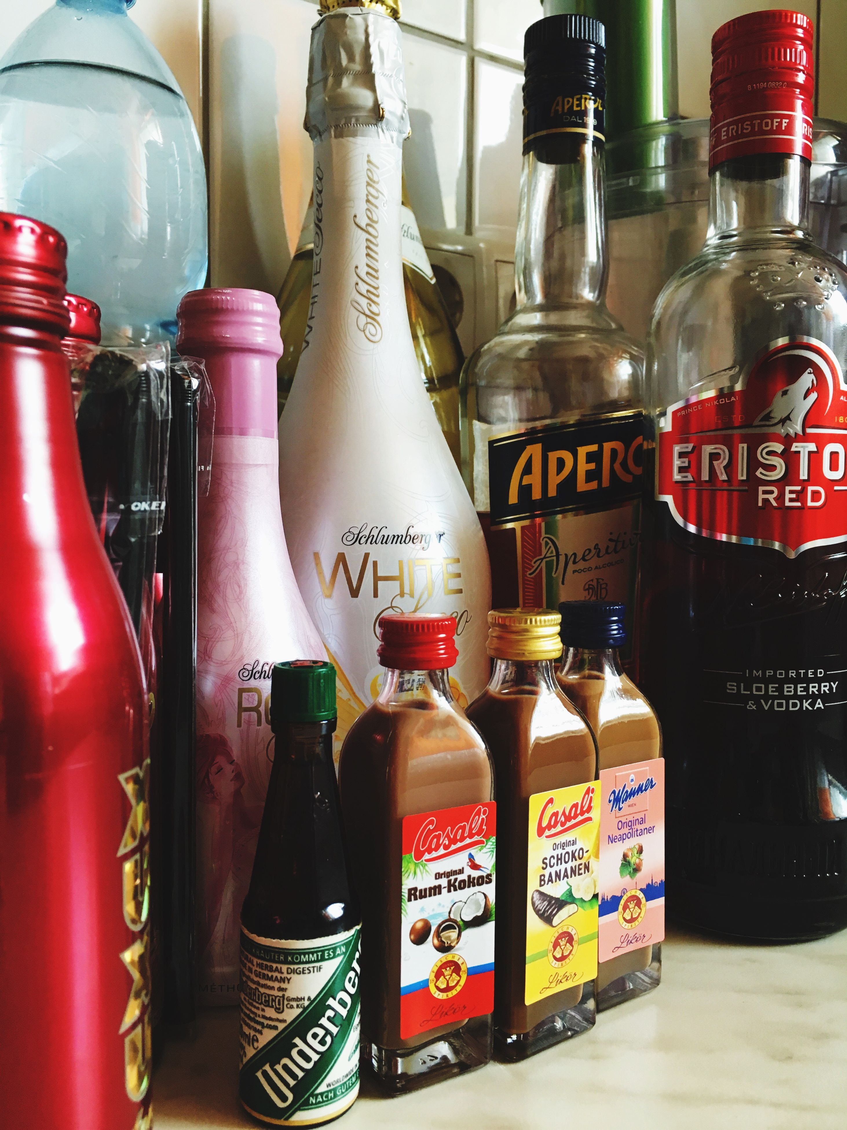 indoors, text, variation, bottle, choice, glass - material, still life, food and drink, western script, communication, large group of objects, drink, arrangement, shelf, close-up, container, abundance, red, transparent, no people