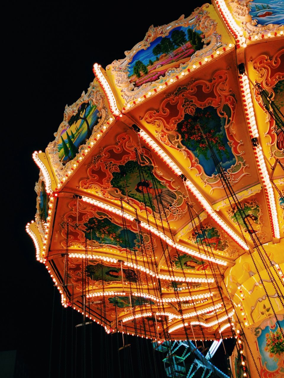 amusement park, low angle view, arts culture and entertainment, night, illuminated, amusement park ride, built structure, no people, carousel, architecture, outdoors, sky, close-up