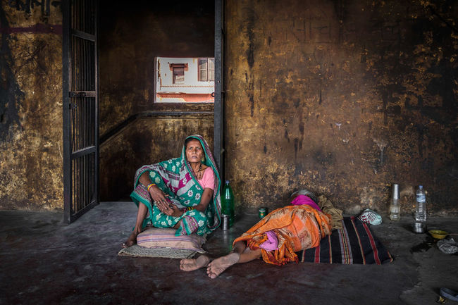 Varanasi is a holy city and is regarded as the last sto before Nirvana. People go there to die, believing that dying in this holy place will release them from the cycle of rebirth. In this image, a daughter sits beside her dying mother in a hostel at Manikarnika Ghat, the cremation or burning ghat. The Photojournalist - 2016 EyeEm Awards Varanasi India