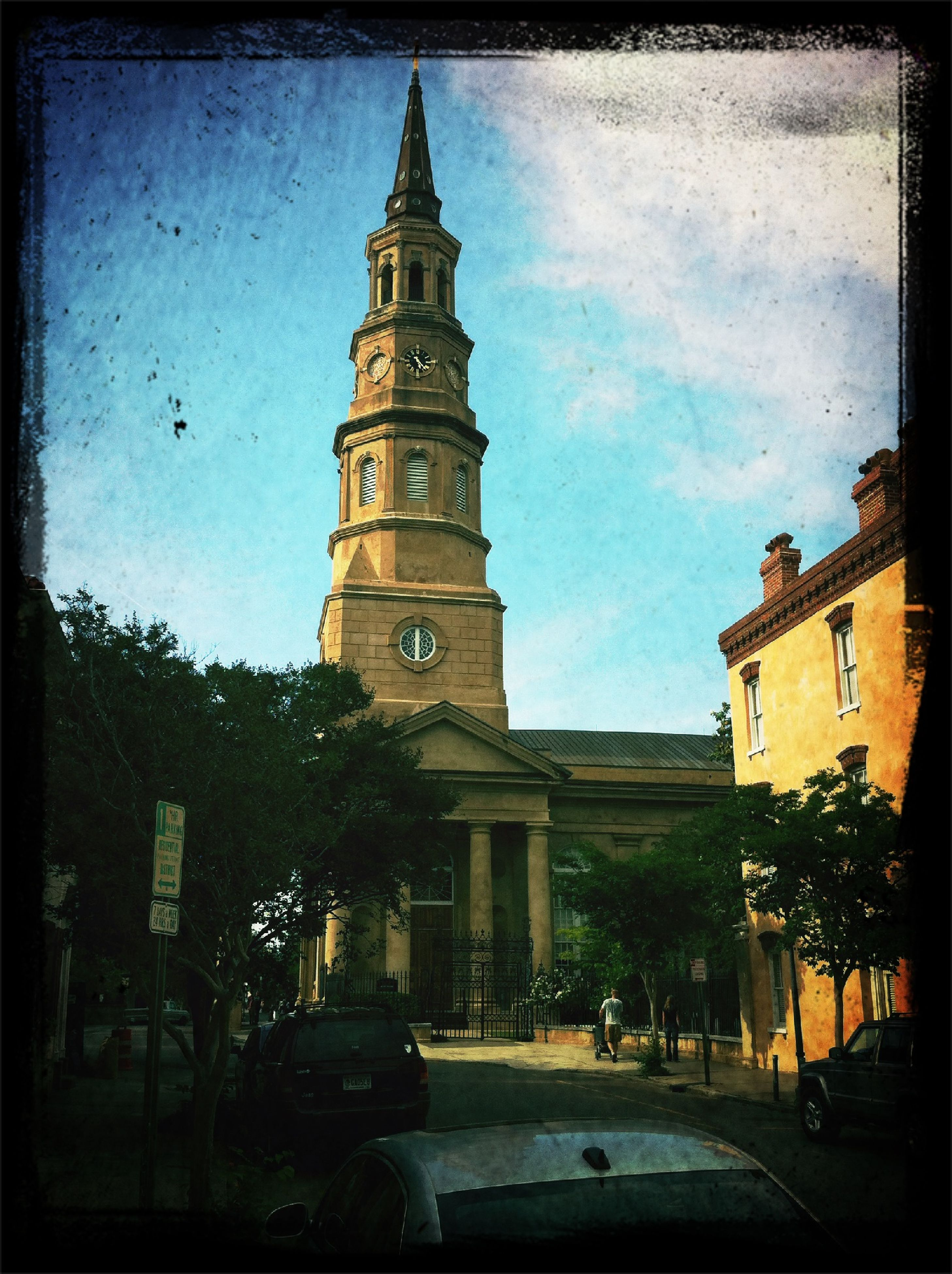 building exterior, architecture, built structure, transfer print, auto post production filter, sky, tree, low angle view, city, tower, clock tower, history, church, incidental people, religion, street, travel destinations, outdoors, car, place of worship