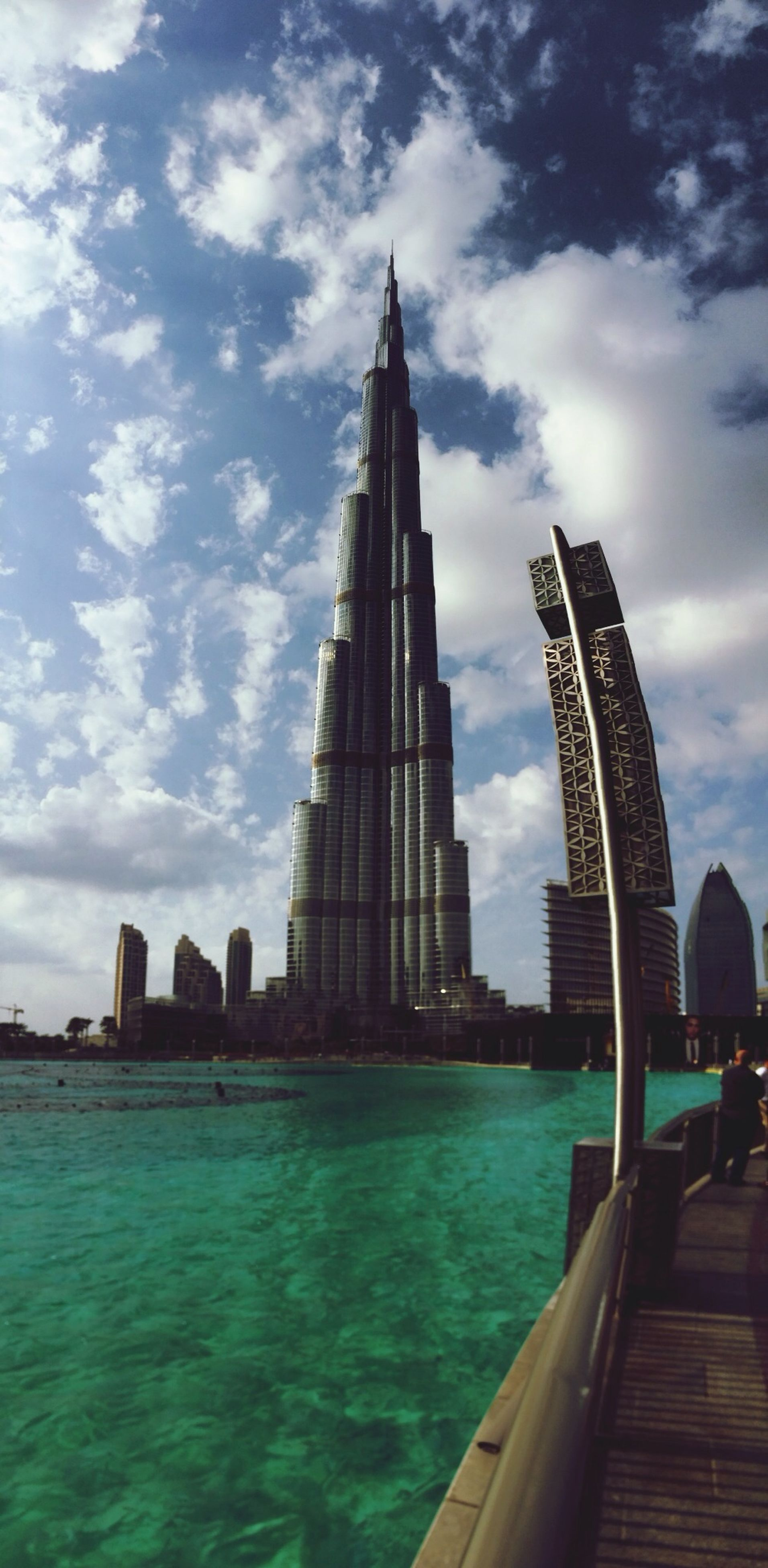 architecture, built structure, building exterior, sky, water, famous place, city, cloud - sky, travel destinations, tourism, international landmark, travel, tower, capital cities, cloud, tall - high, waterfront, skyscraper, cloudy, modern