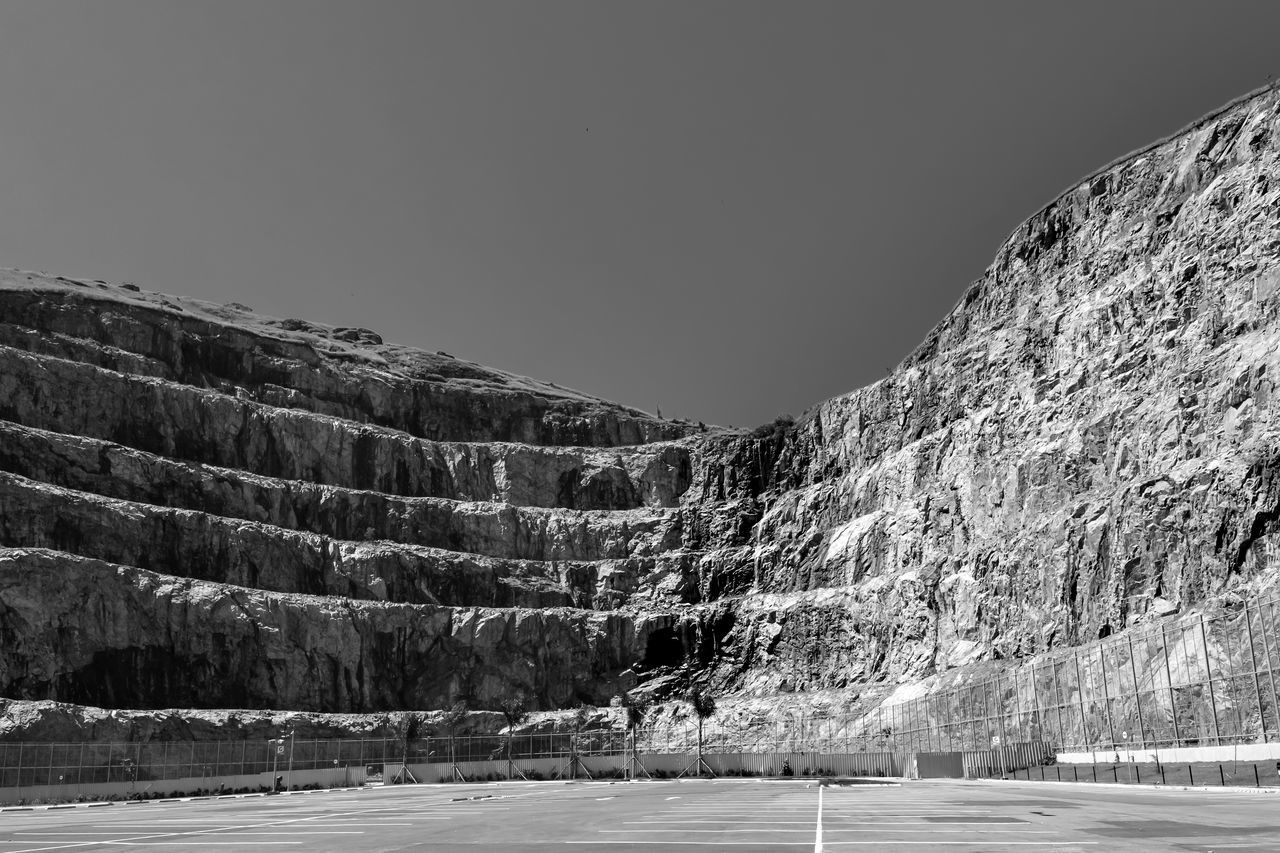 An old quarry turned into a parking area of a mall. Bw Day Landscape Mountain Nature No People Parking Area Quarry Sky