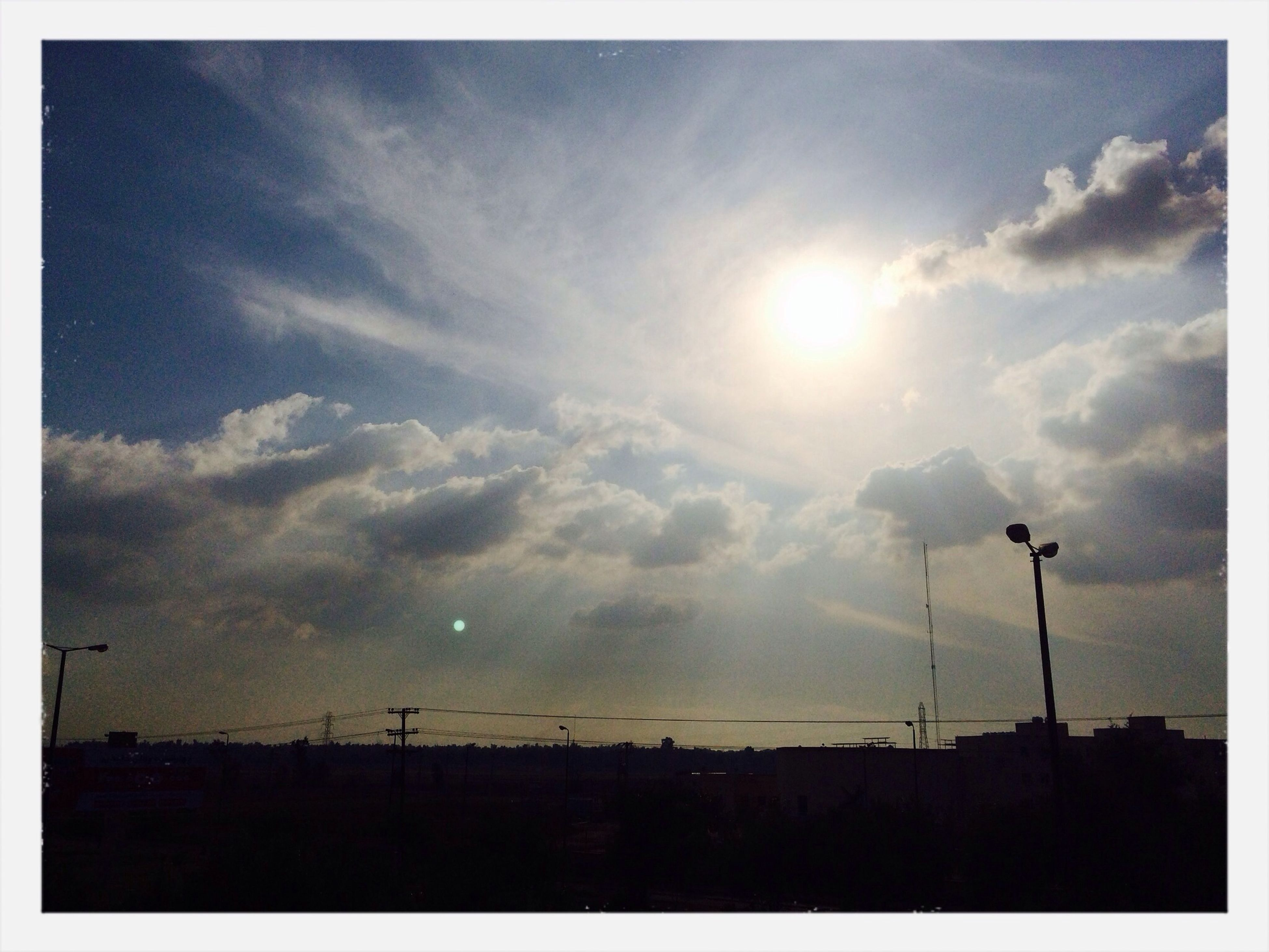 sky, silhouette, transfer print, sun, cloud - sky, sunset, sunbeam, low angle view, sunlight, cloud, cloudy, auto post production filter, beauty in nature, street light, nature, scenics, building exterior, built structure, tranquility, outdoors