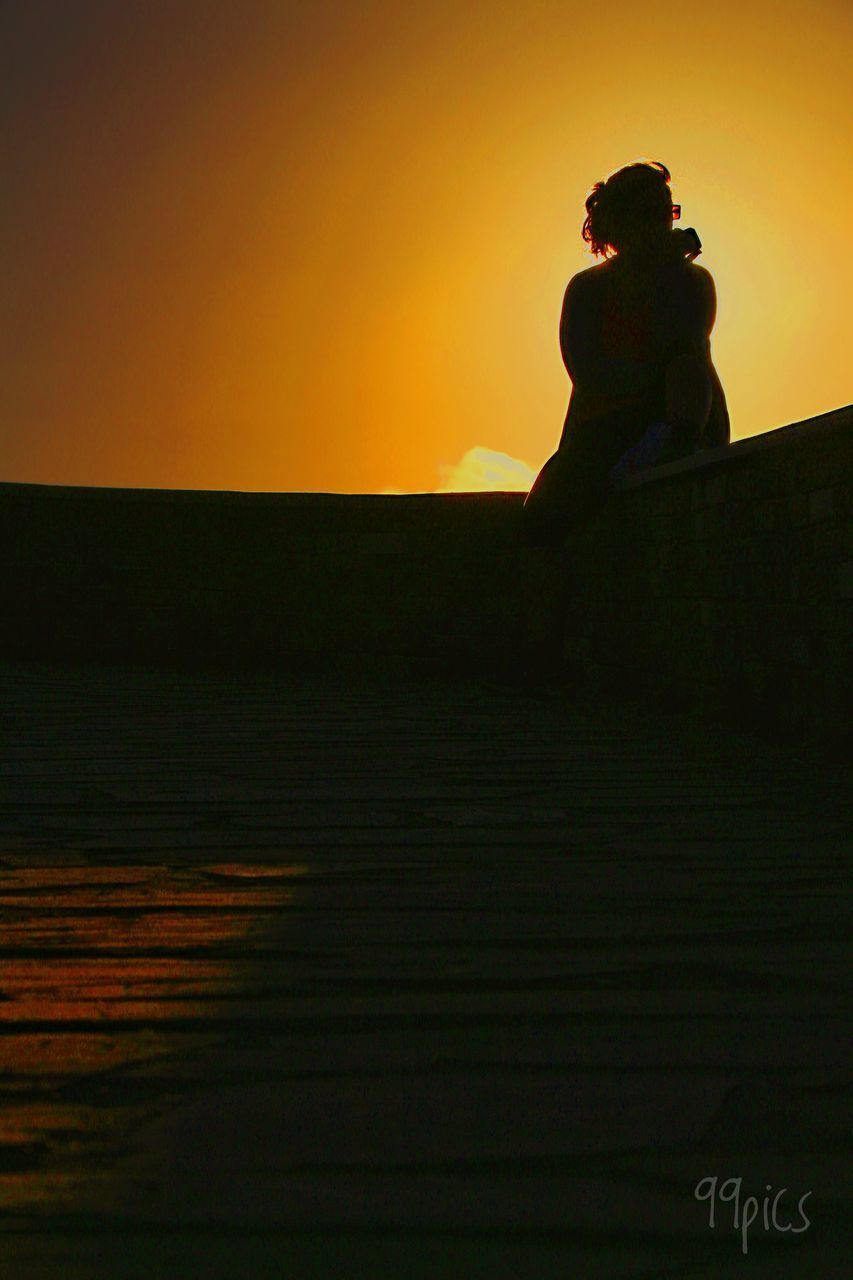 sunset, real people, lifestyles, nature, leisure activity, outdoors, silhouette, full length, scenics, beauty in nature, standing, vacations, sky, clear sky, sea, one person, young women, water, young adult, day, people
