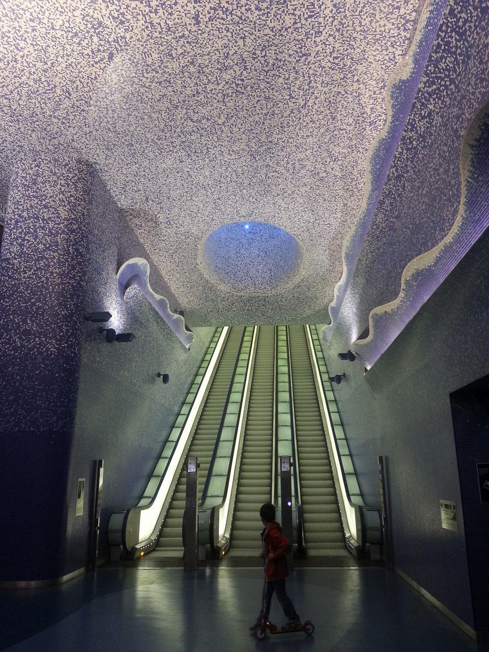 Boy By Illuminated Escalator In Modern Building