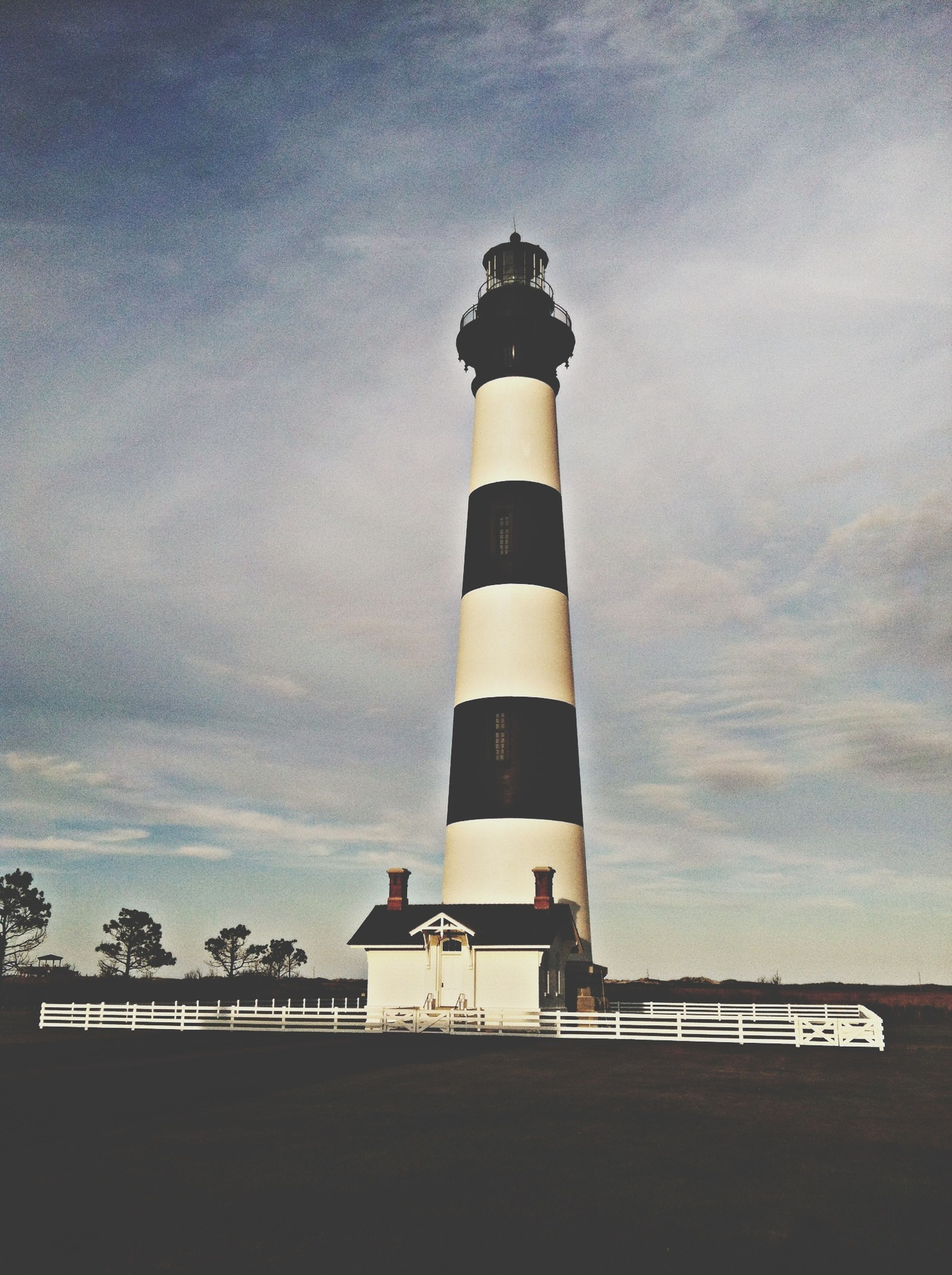 lighthouse, guidance, sky, built structure, architecture, direction, building exterior, protection, safety, sea, cloud - sky, tower, security, low angle view, tranquility, nature, outdoors, no people, tranquil scene, cloudy