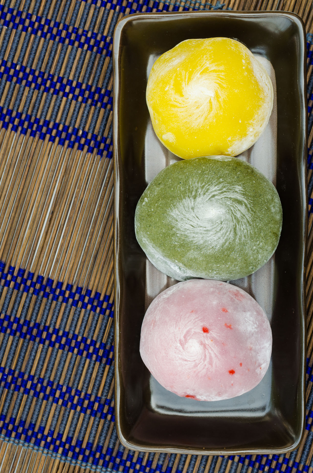 Japanese sweet made of sticky rice flour and black bean. DAIFUKU candy dish on bamboo mat. Appetizer Baked Bamboo Closeupshot Colorful Daifuku Dango Decorated Food Desserts Flour Food Freshness Green Color Icing Sugar Japanese Food Mat No People Pink Color Snack Soft Sprinkle Traditionalfood Yellow Color