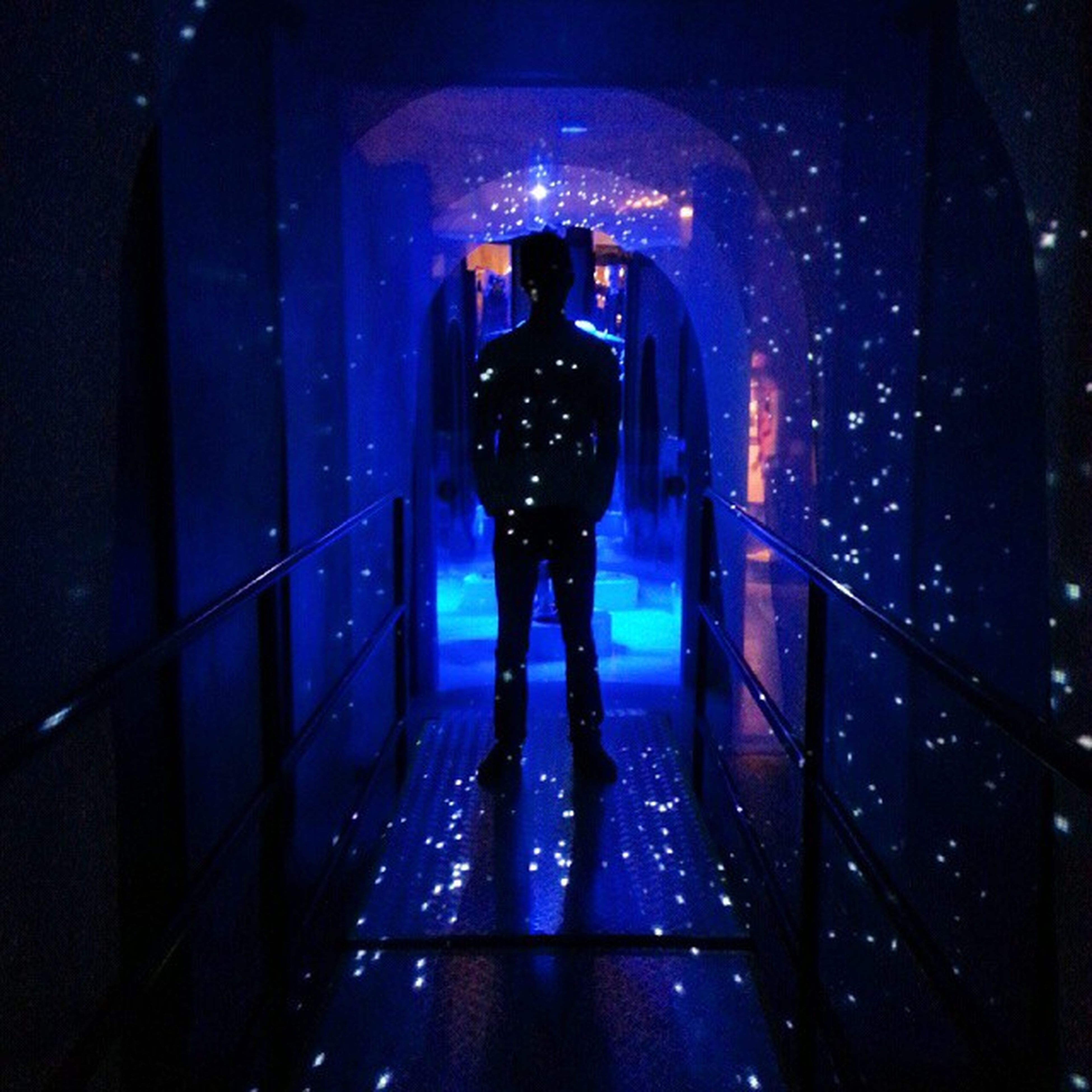 full length, indoors, lifestyles, walking, architecture, rear view, built structure, leisure activity, men, standing, illuminated, night, casual clothing, tunnel, person, silhouette, wall - building feature, reflection