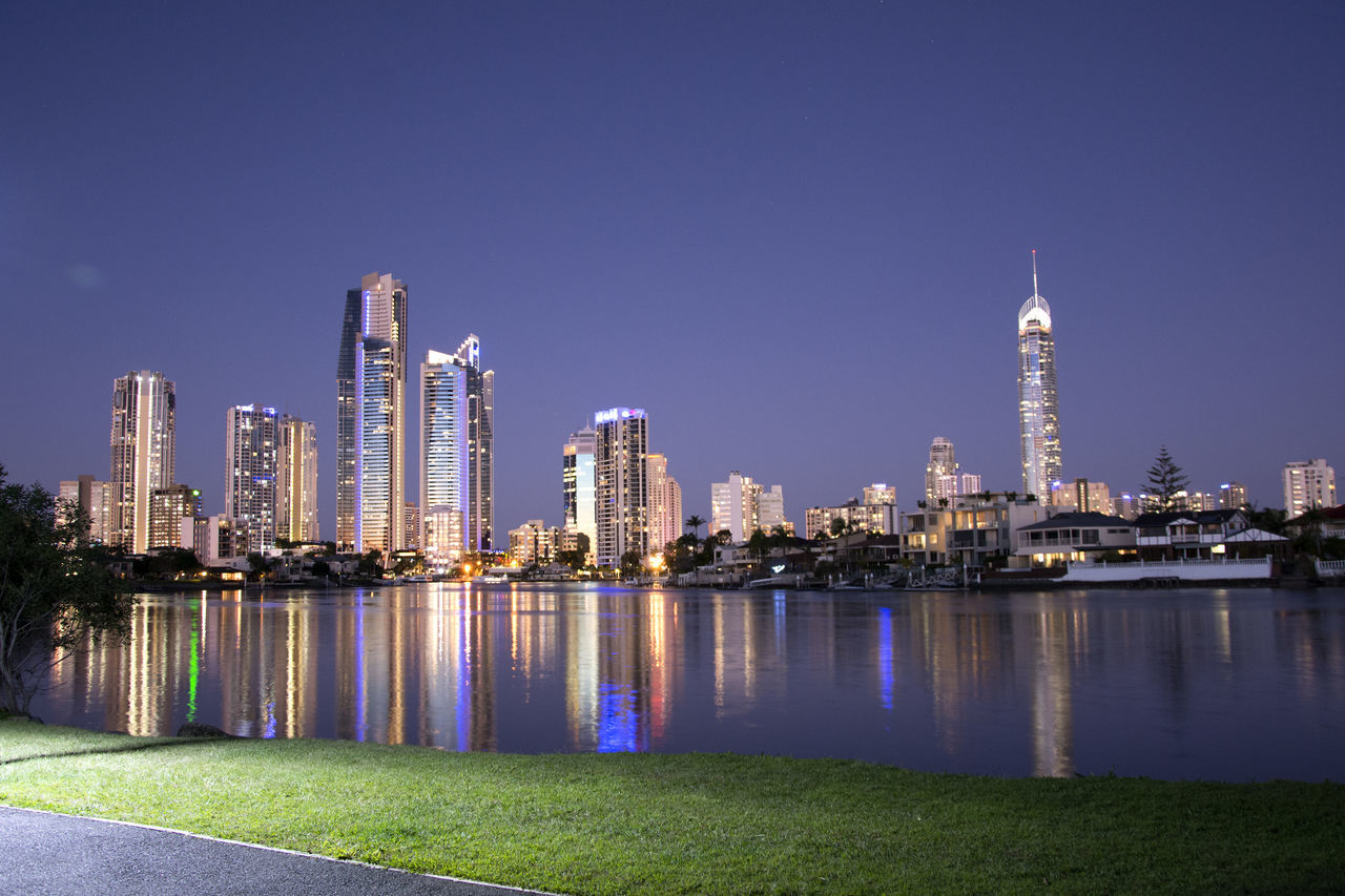 Scenic View Of Lake And Illuminated Cityscape Against Sky At Dusk