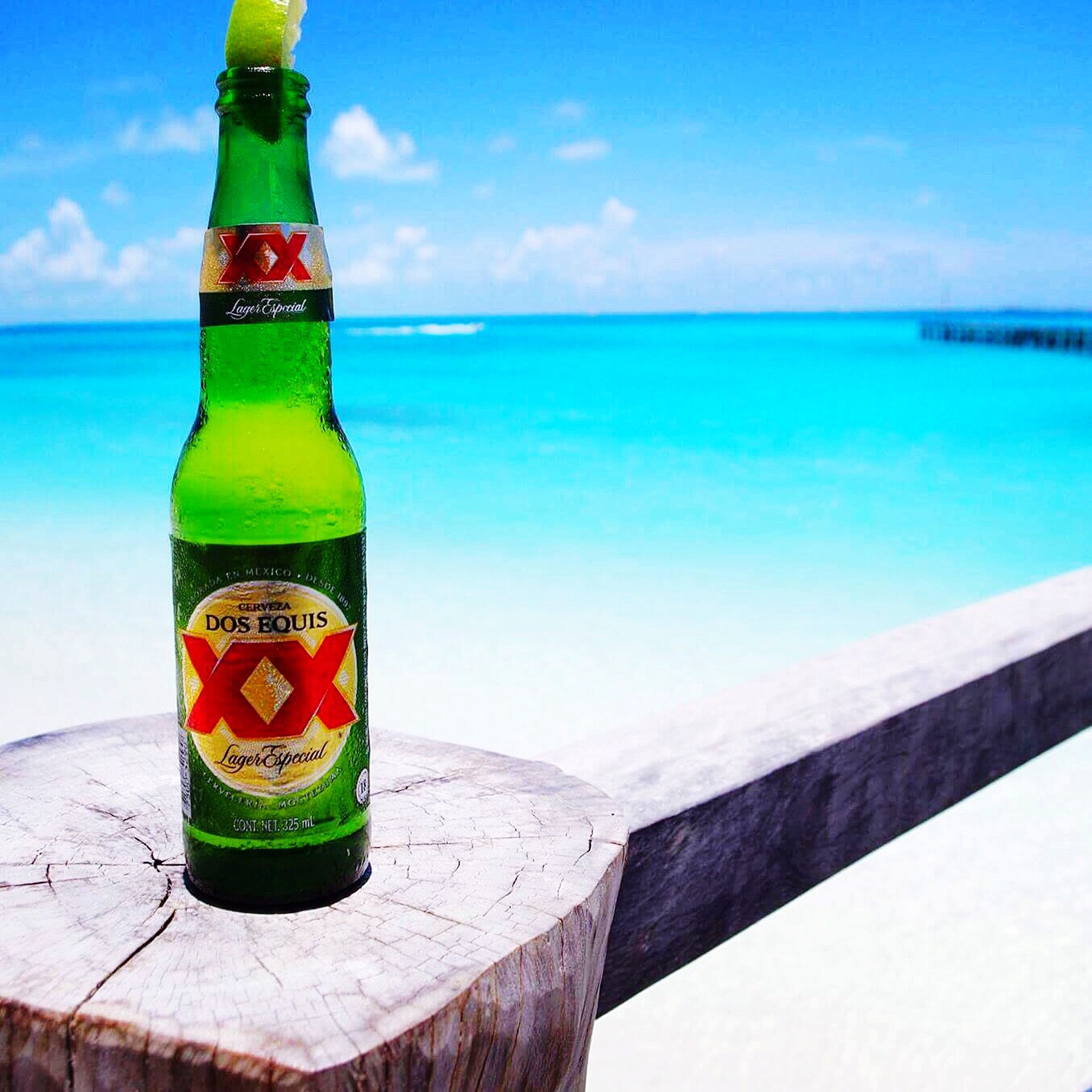 blue, green color, sea, no people, water, sky, swimming pool, drink, cloud - sky, food and drink, alcohol, freshness, outdoors, close-up, beauty in nature, drinking glass, nature, vacations, day