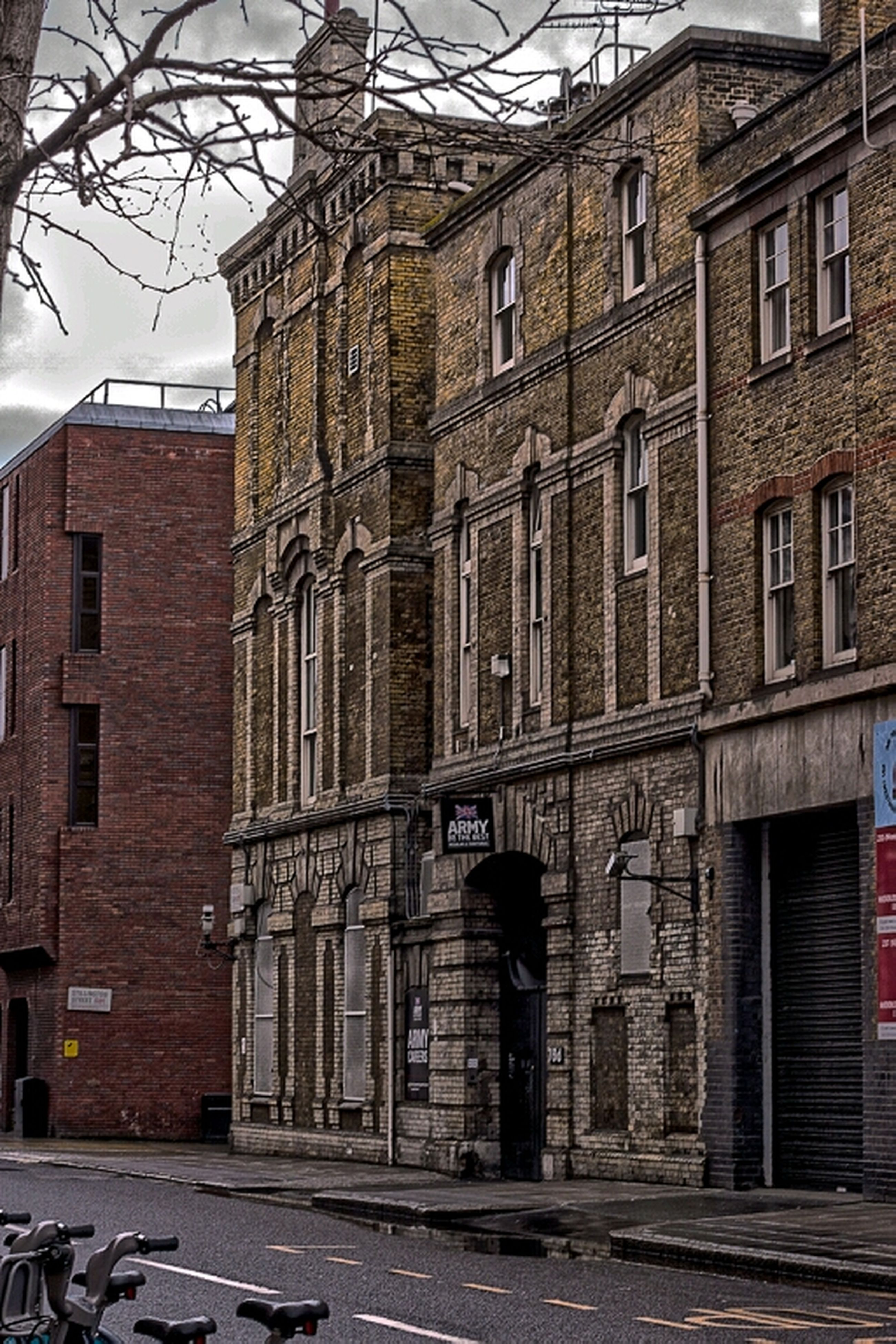 architecture, building exterior, built structure, building, city, bare tree, window, brick wall, low angle view, street, residential building, day, residential structure, outdoors, sky, no people, power line, old, cable, wall - building feature