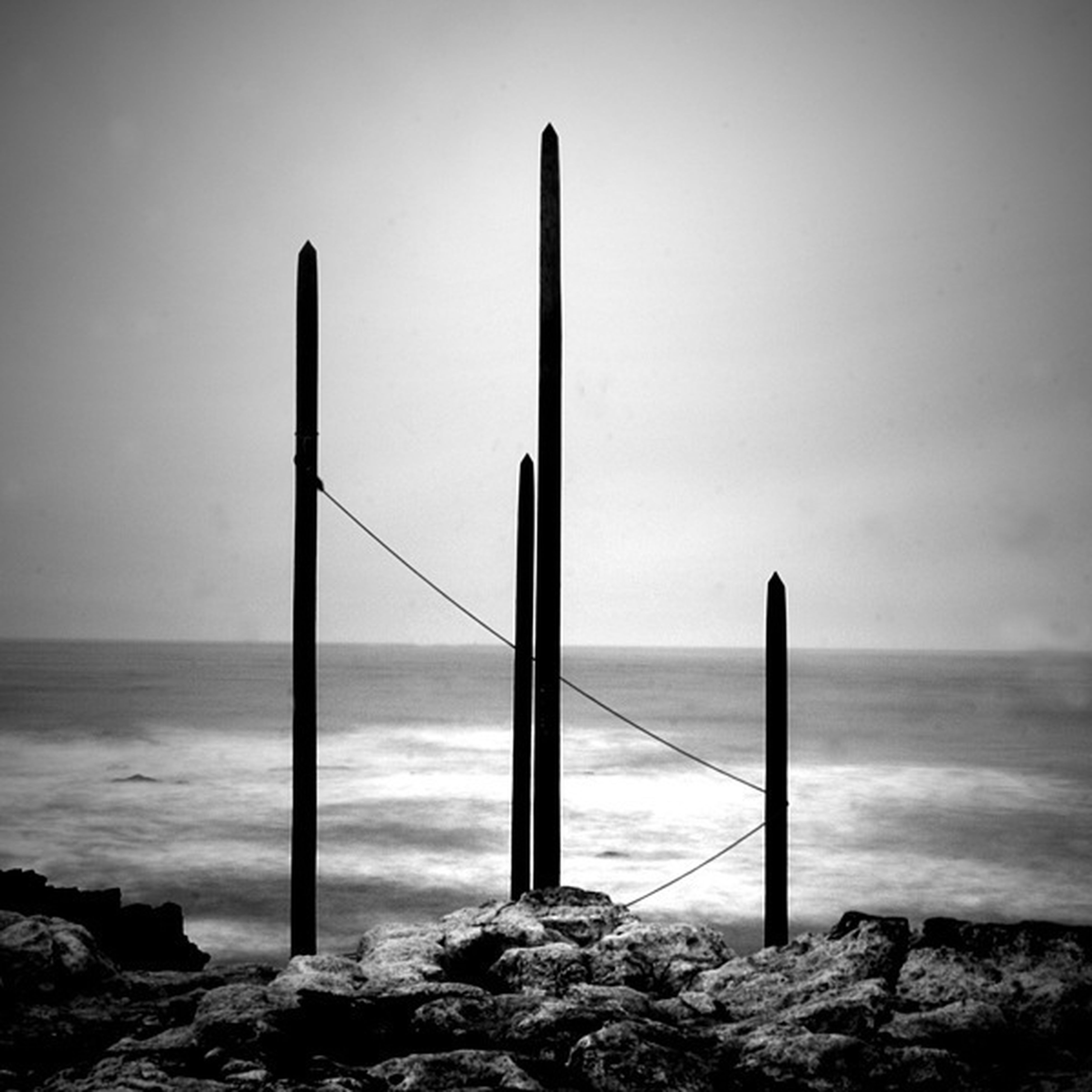 sea, horizon over water, water, beach, sky, shore, clear sky, tranquility, tranquil scene, scenics, nature, rock - object, pole, beauty in nature, wave, no people, day, outdoors, idyllic, wooden post