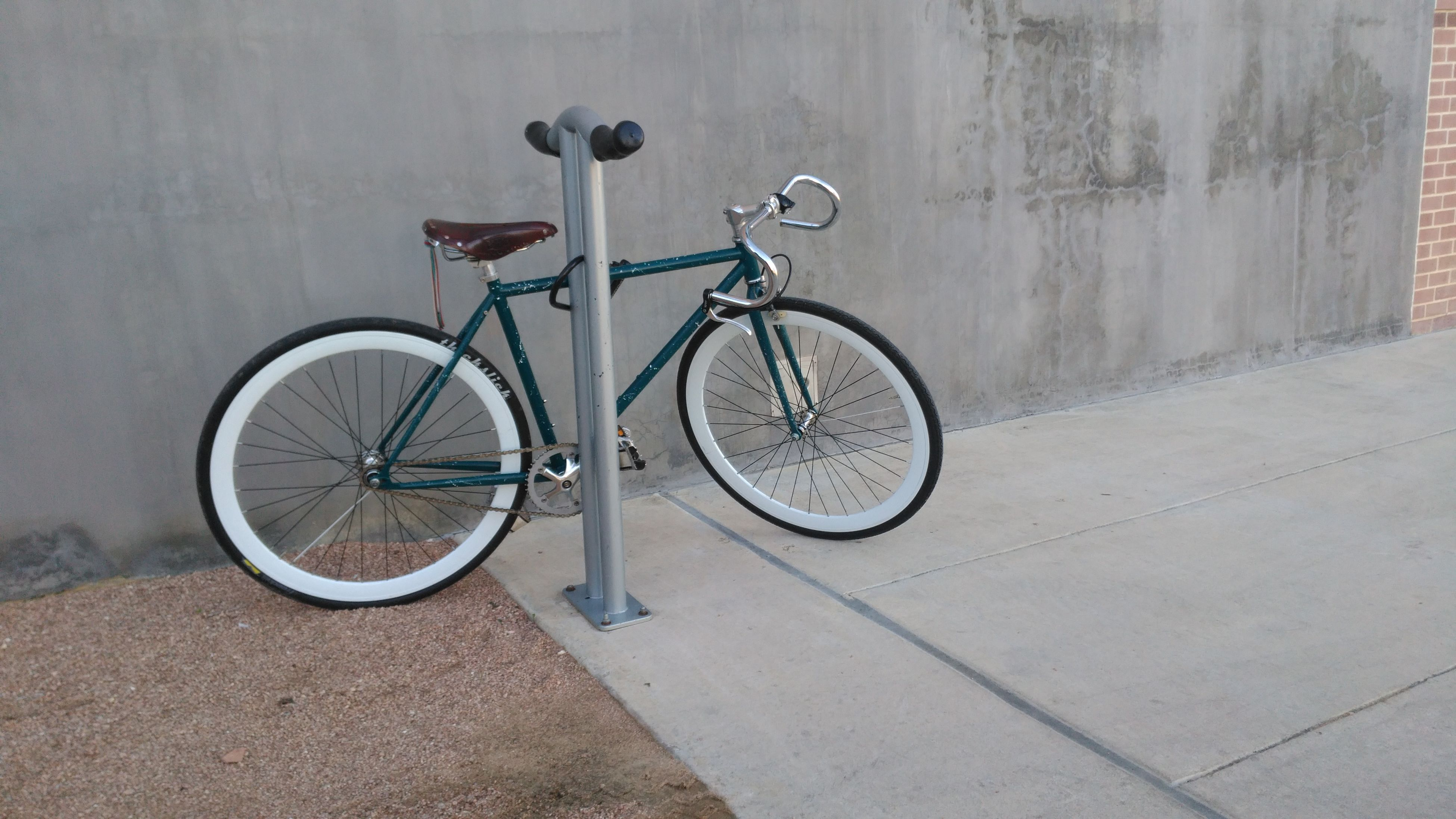 bicycle, transportation, land vehicle, mode of transport, stationary, parked, parking, wall - building feature, street, built structure, sidewalk, wall, architecture, wheel, day, cycle, no people, outdoors, road, building exterior