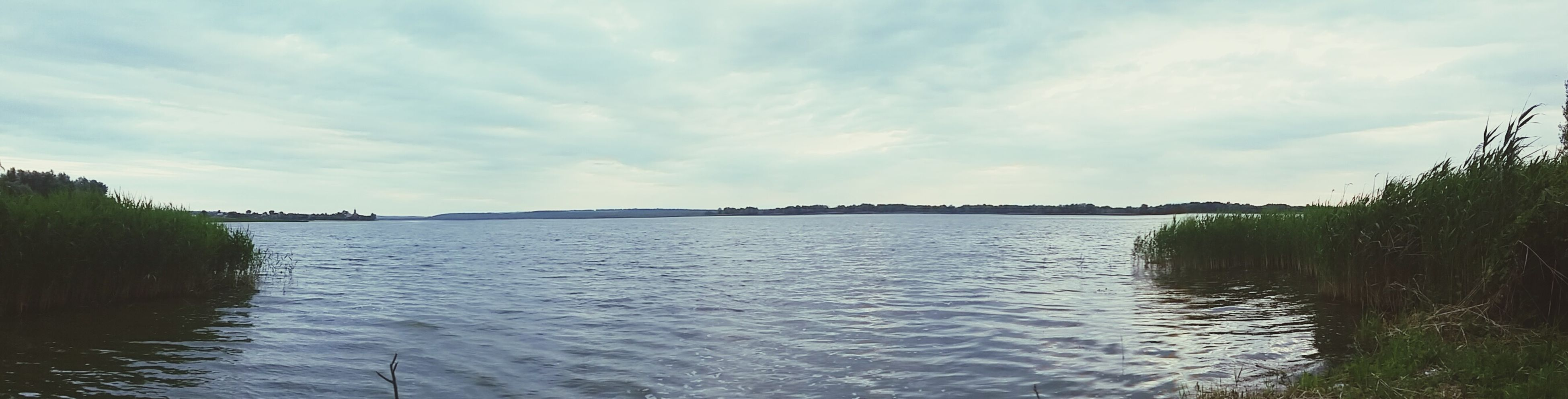 water, sky, tranquil scene, waterfront, cloud - sky, tranquility, scenics, beauty in nature, cloudy, nature, rippled, tree, cloud, lake, river, idyllic, day, outdoors, non-urban scene, sea