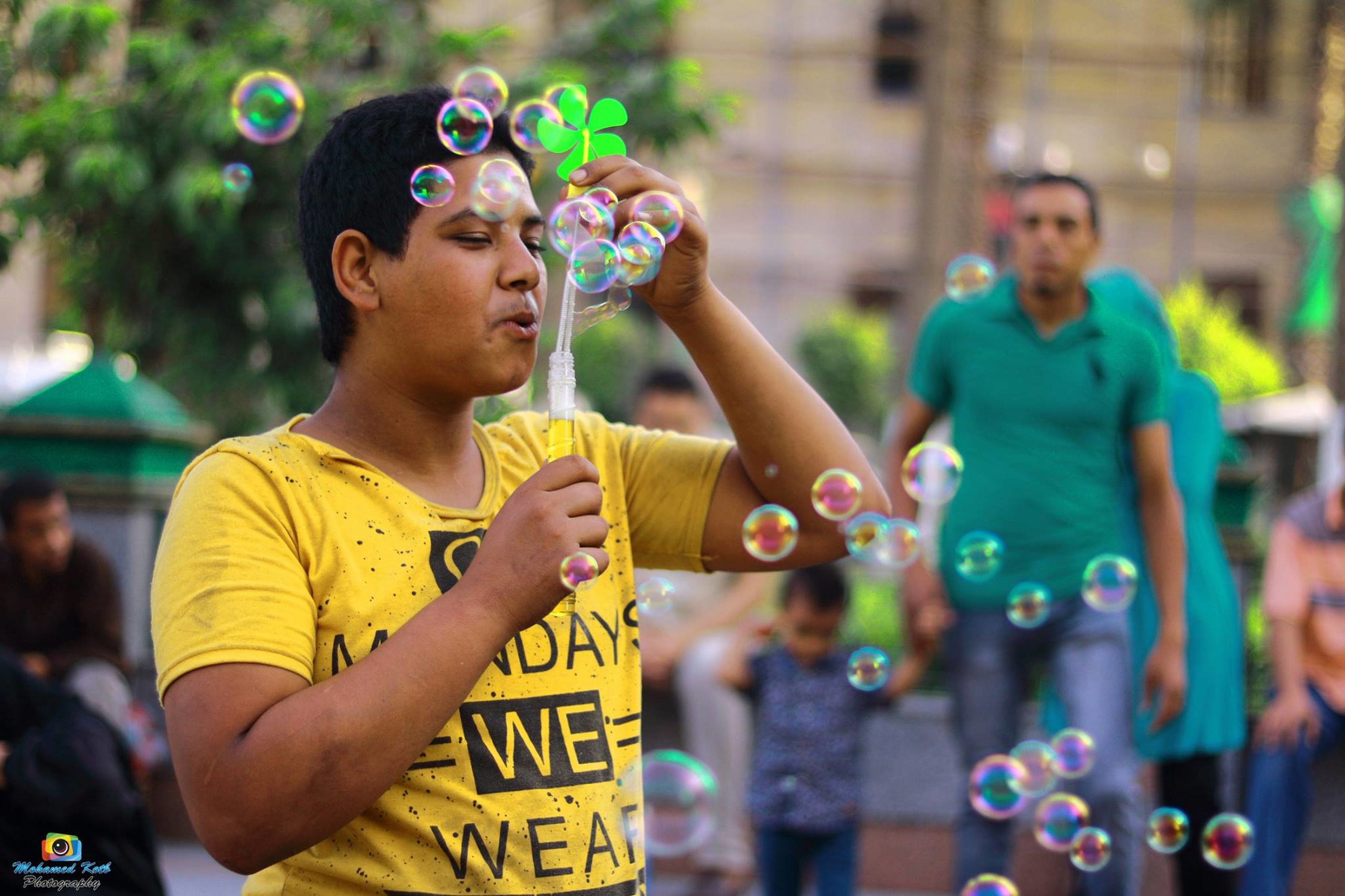 blowing, bubble, bubble wand, casual clothing, real people, focus on foreground, leisure activity, day, outdoors, fun, holding, lifestyles, young adult, adult, adults only, people