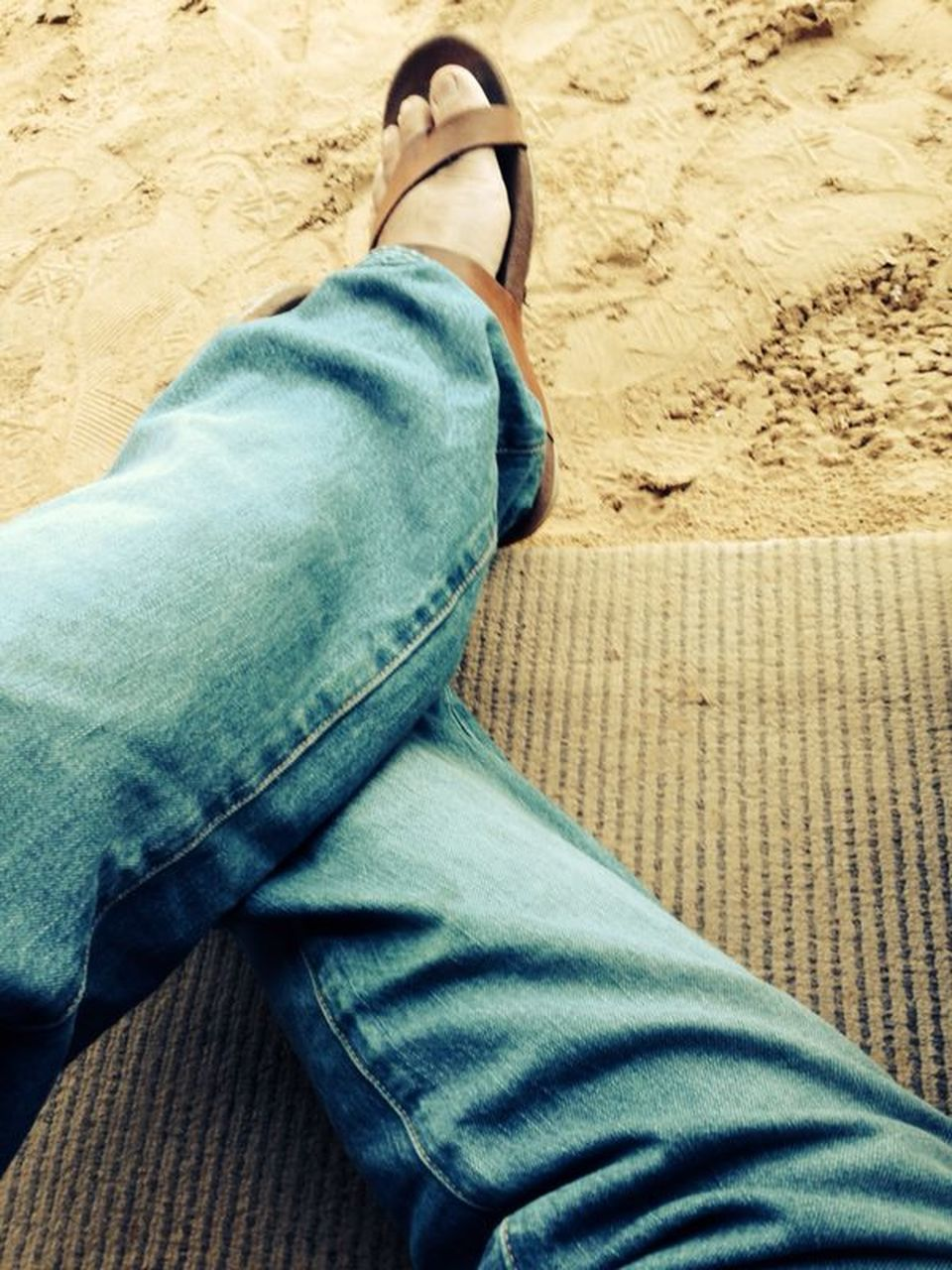 low section, human leg, jeans, one person, real people, personal perspective, casual clothing, human body part, sand, leisure activity, high angle view, shoe, lifestyles, relaxation, day, men, sitting, indoors, beach, close-up, adult, people