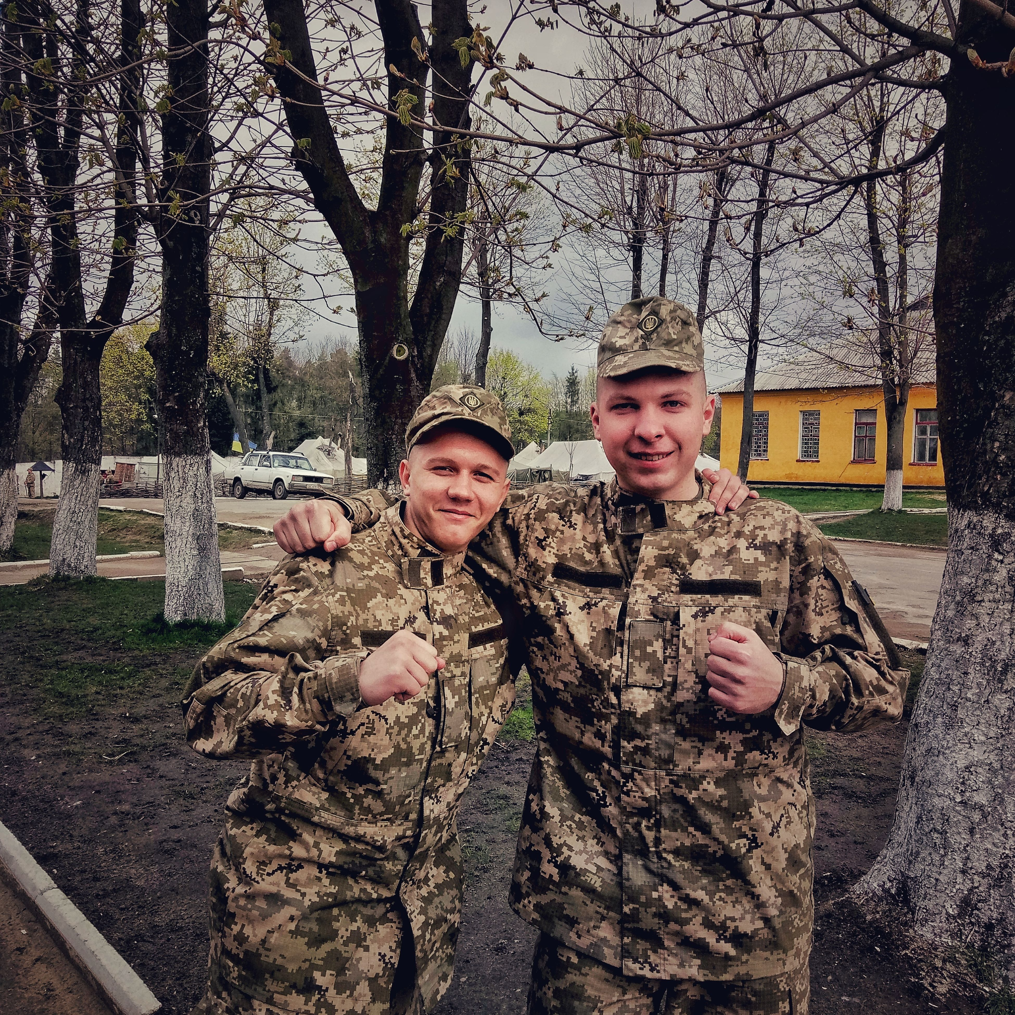 looking at camera, portrait, child, boys, childhood, two people, smiling, happiness, males, people, lifestyles, togetherness, family, military uniform, leisure activity, cheerful, friendship, tree, outdoors, military, adult, army, camouflage clothing, day