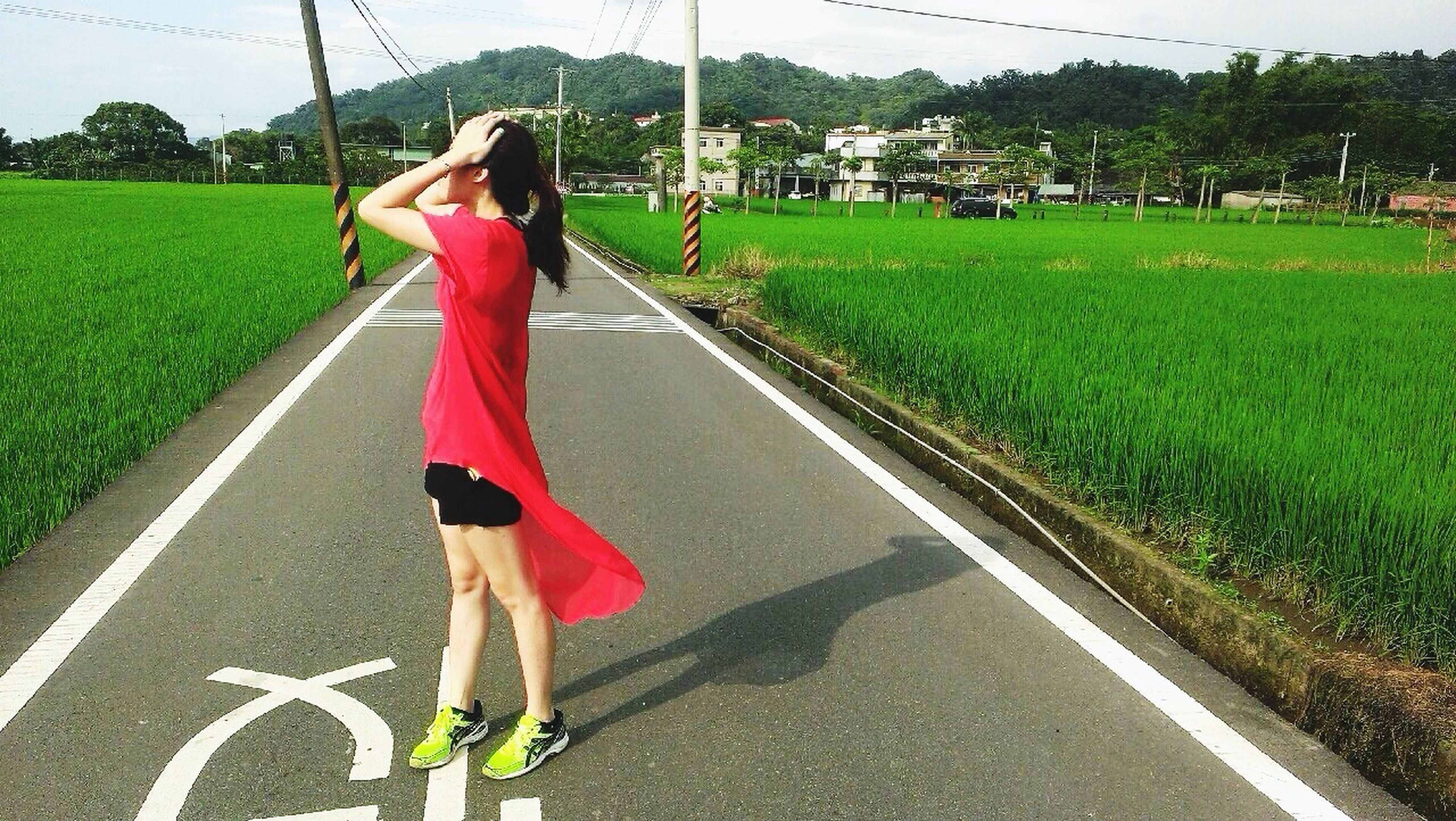 road, grass, transportation, lifestyles, full length, leisure activity, the way forward, casual clothing, street, road marking, walking, field, diminishing perspective, rear view, day, vanishing point, outdoors, sunlight