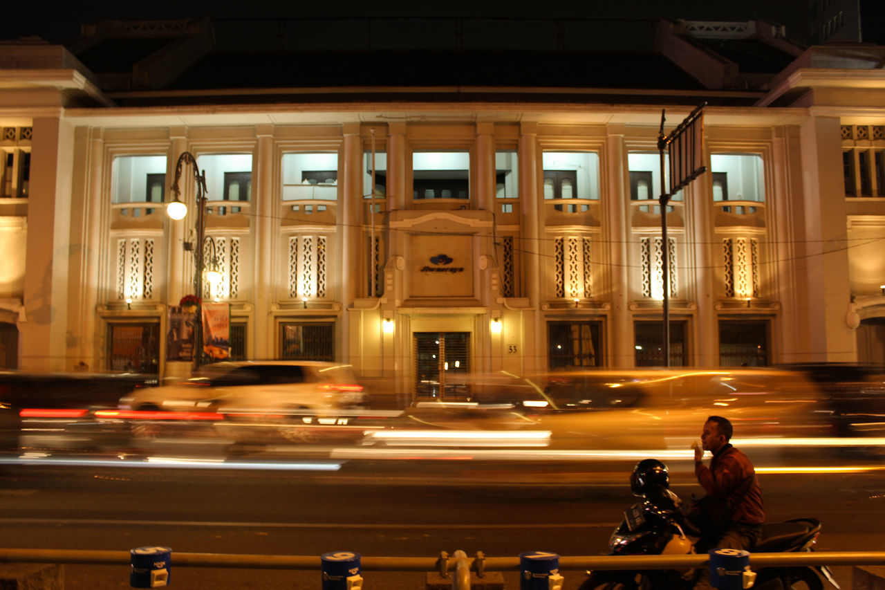 night, illuminated, city, street, architecture, built structure, blurred motion, city life, city street, building exterior, transportation, motion, land vehicle, road, real people, architectural column, outdoors, biker, people