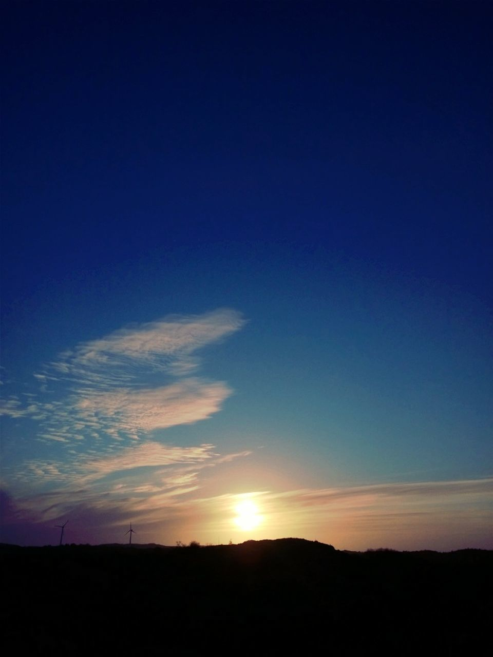 Silhouette landscape against blue sky at sunset