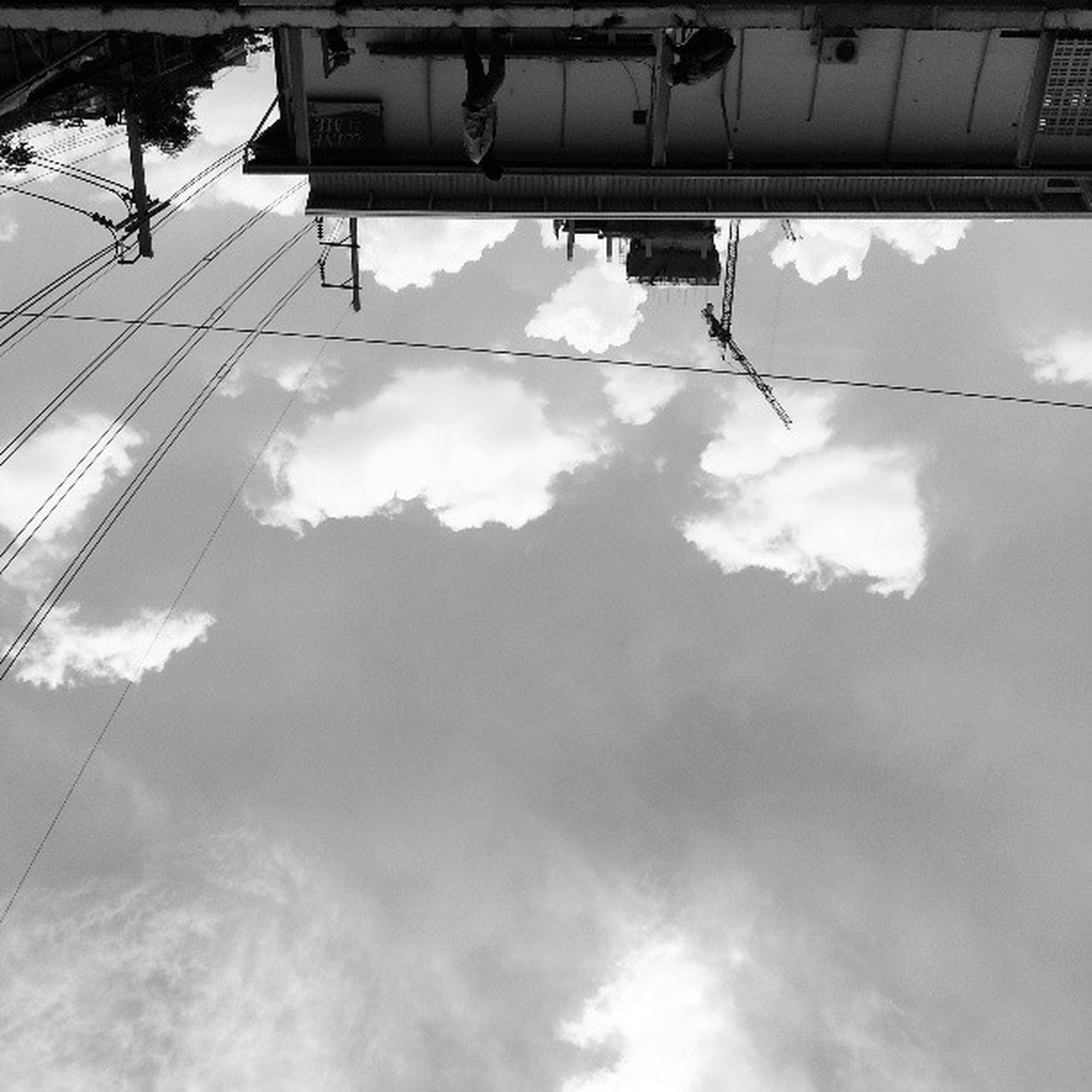 low angle view, power line, sky, cloud - sky, electricity, cable, power supply, electricity pylon, connection, tree, built structure, cloudy, architecture, cloud, building exterior, day, fuel and power generation, power cable, technology, no people