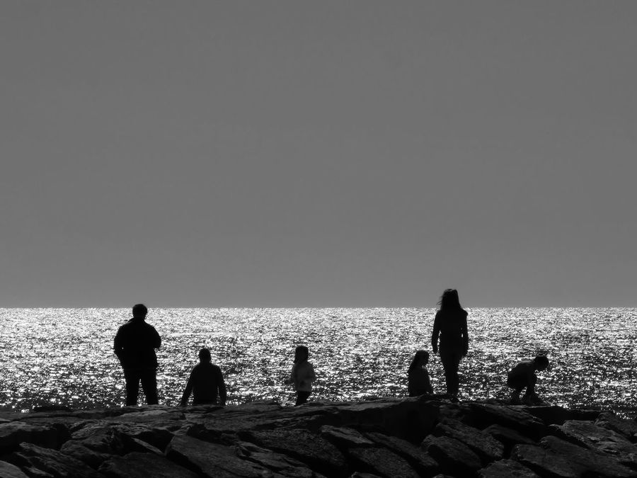 Adult Backlighting Backlighting Photography Beach Beauty In Nature Black And White Clear Sky Day Horizon Over Water Men Nature Outdoors People Real People Sea Silhouettes Sky Togetherness Tranquil Scene Water