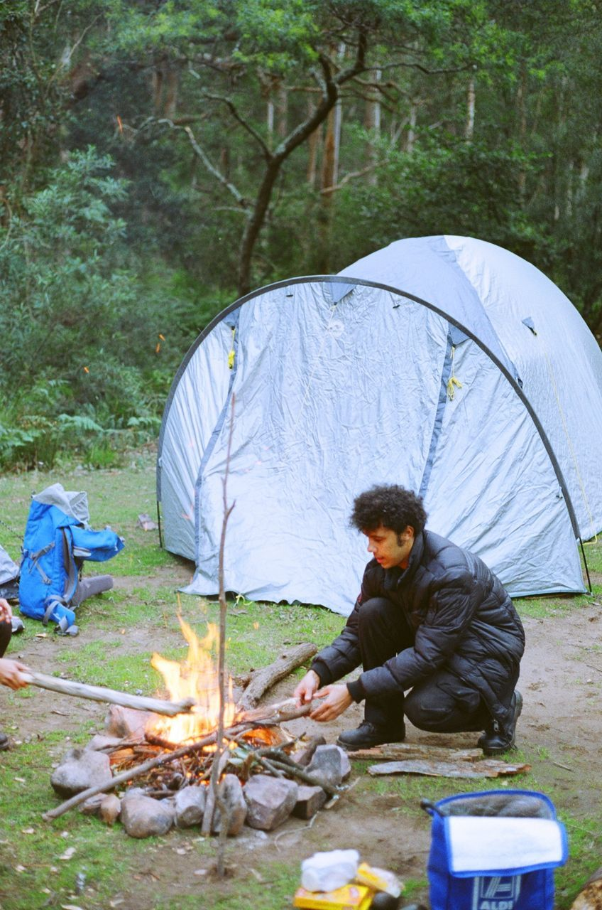 camping, tent, sitting, men, outdoors, one man only, one person, day, full length, people, real people, adult, adults only, food, nature, only men