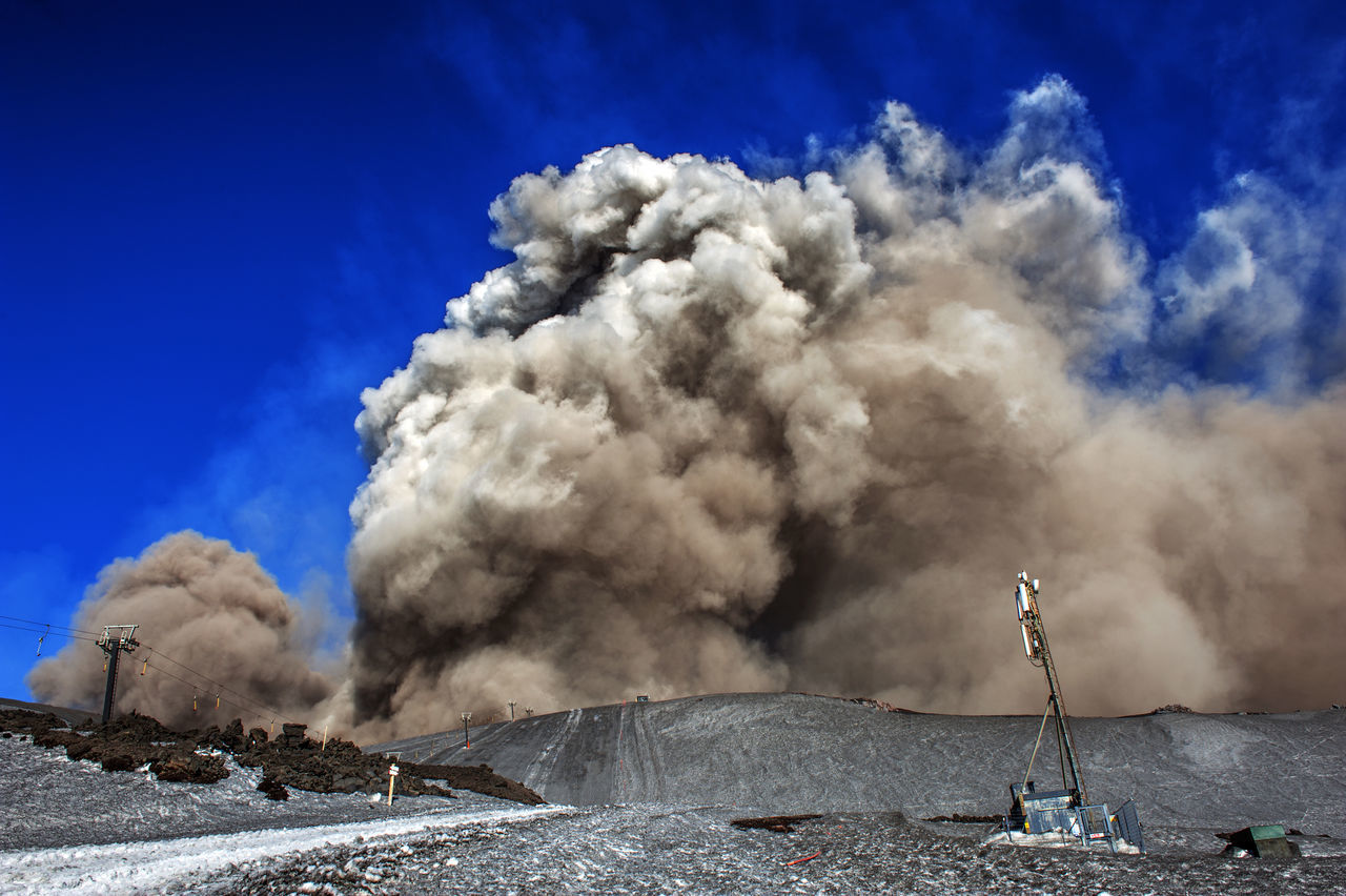 smoke - physical structure, emitting, outdoors, geology, blue, erupting, sky, day, smoke stack, industry, heat - temperature, nature, accidents and disasters, volcanic crater, no people, landscape, beauty in nature, factory
