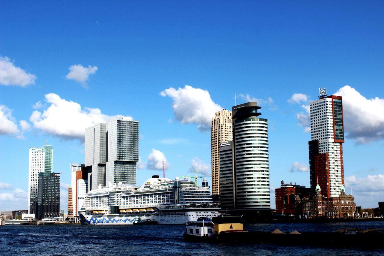Cruise Ship On Sea By Modern Buildings Against Sky